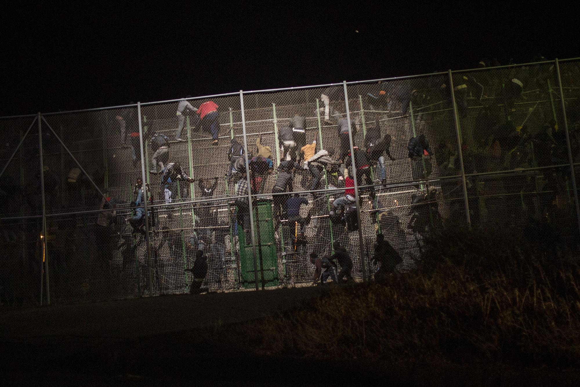 Sub-Saharan migrants scale a metallic fence that divides Morocco and the Spanish enclave of Melilla, early in the morning on Wednesday, May 28, 2014. More than 400 African migrants managed to jump the barbed-wire border fence in SpainÌs North African enclave of Melilla, hundreds of others were blocked and beaten back by Moroccan police while the rest were pushed back by the Spanish Guardia Civil. During the pre-dawn border storming, cries of pain and noises of people being hit could be heard as police from both sides tried to prevent dozens of the sub-Saharan migrants from entering the city from Morocco. (© Santi Palacios)