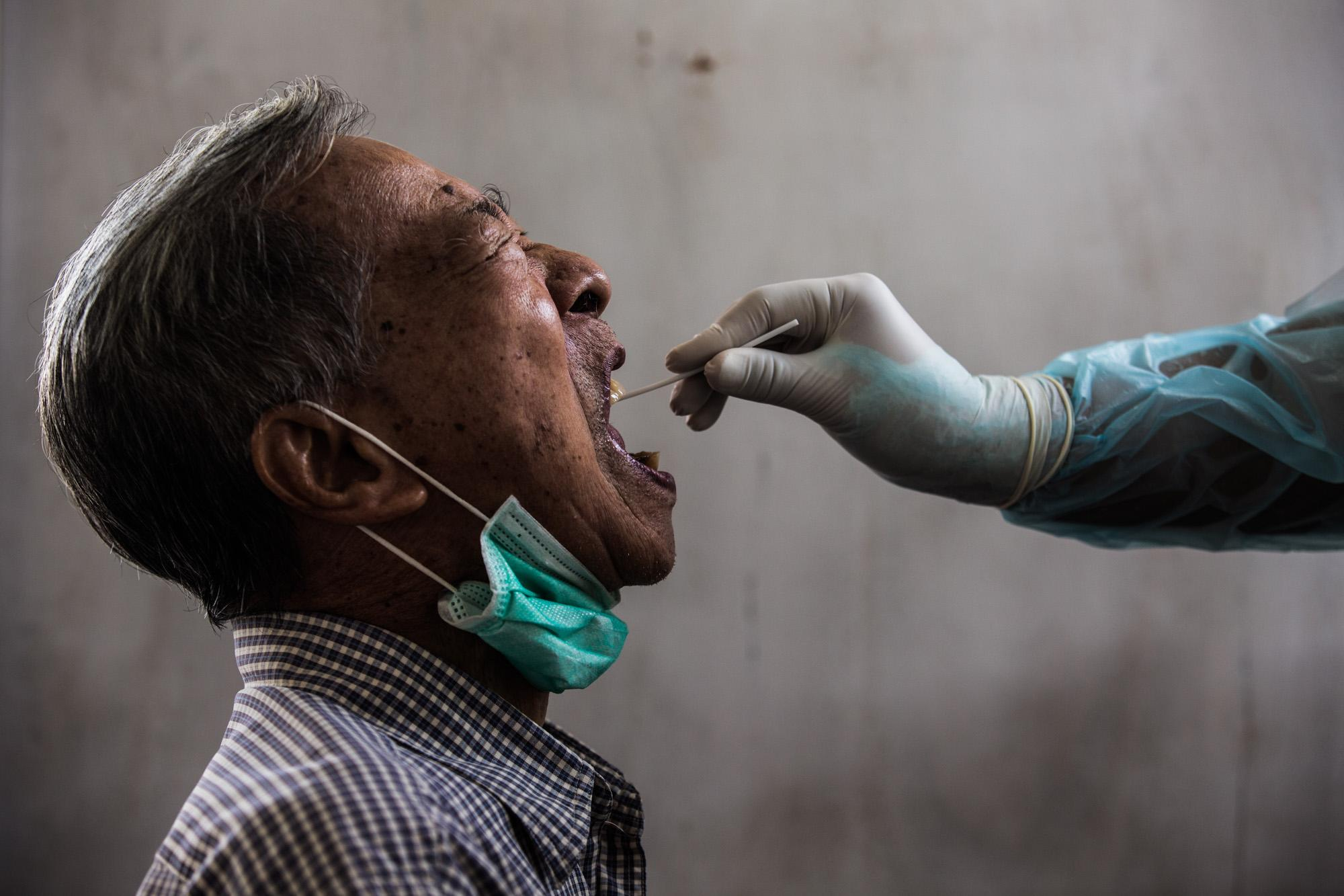 An elderly man is tested for Covid-19 at a small retirement community in Bangkok's Don Muang district.