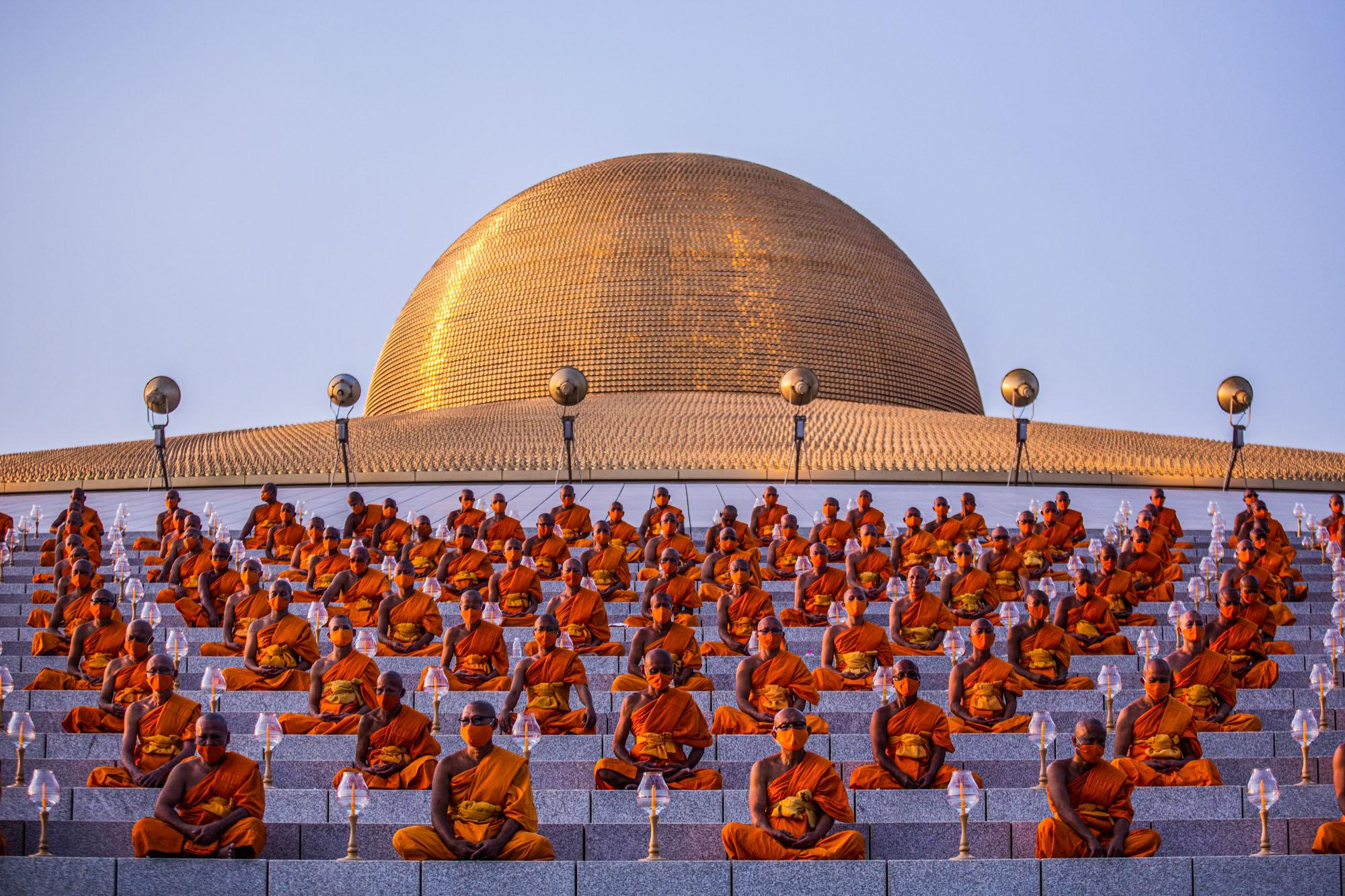 Buddhist monks, wearing face masks, participate in group prayer during Makha Bukha day at Wat Dhammakay.