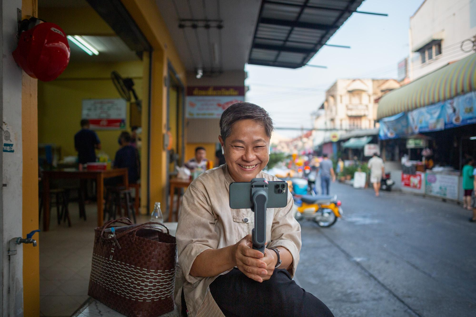Hnoi Latthitham, 53, leads a virtual tour of Chai Chimplee Temple Market in Bangkok, Thailand, on Monday, February 1, 2021, in Bangkok, Thailand. She shows participants the hustle and bustle of morning life, and stops to explain rituals of alms giving to Buddhist monks.