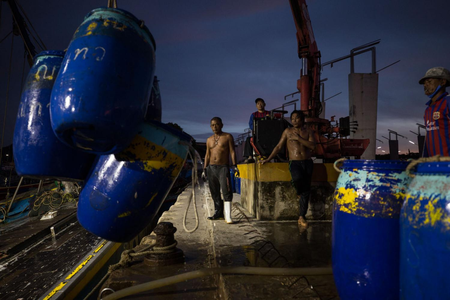 Trawler fishermen unload their catch at dawn at Phukets main fishing harbour. Thailand.