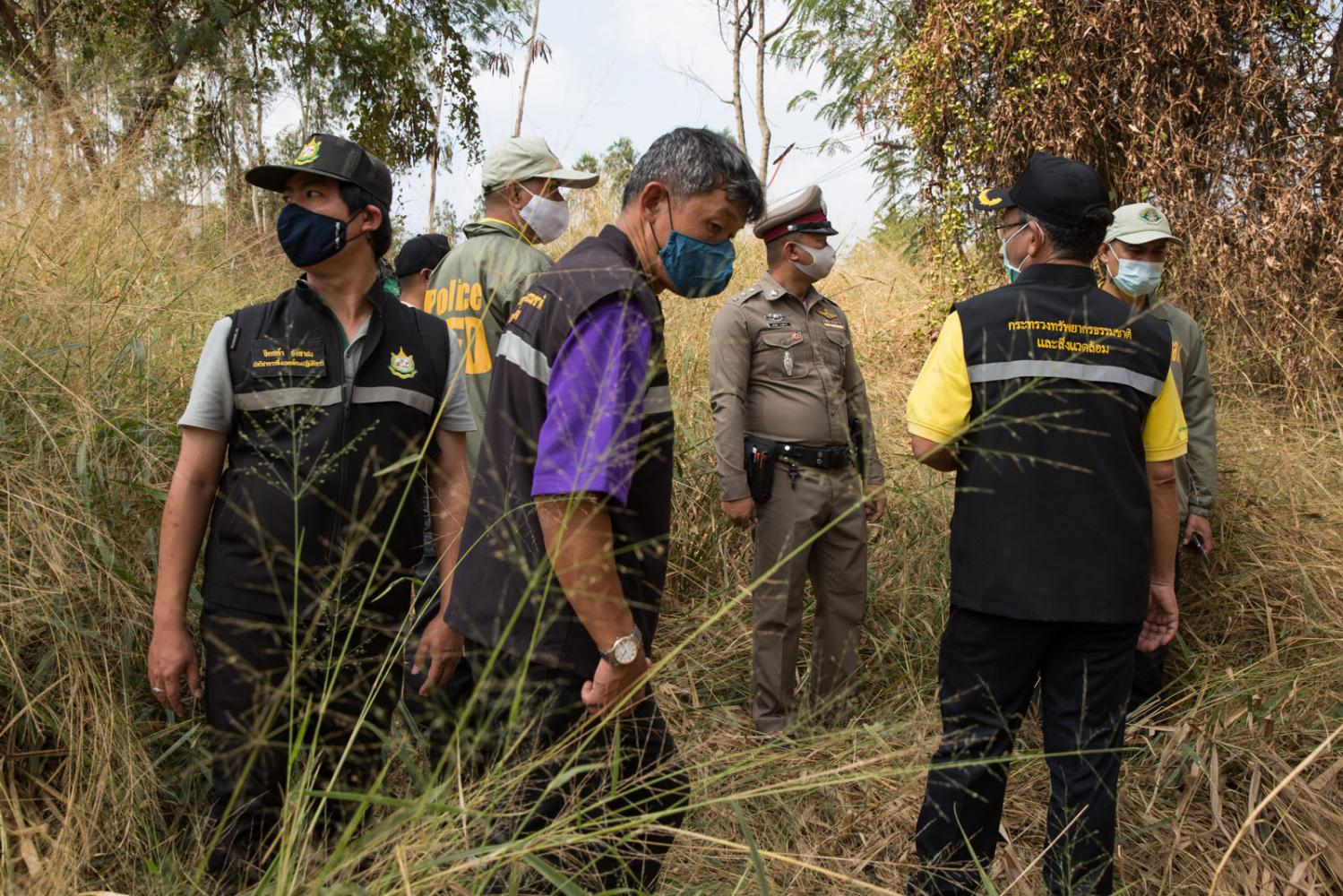 Police and environmental officials inspect an area of land that a recycling plant located nearby has allegedly polluted. Chachoegnsao, Thailand.
