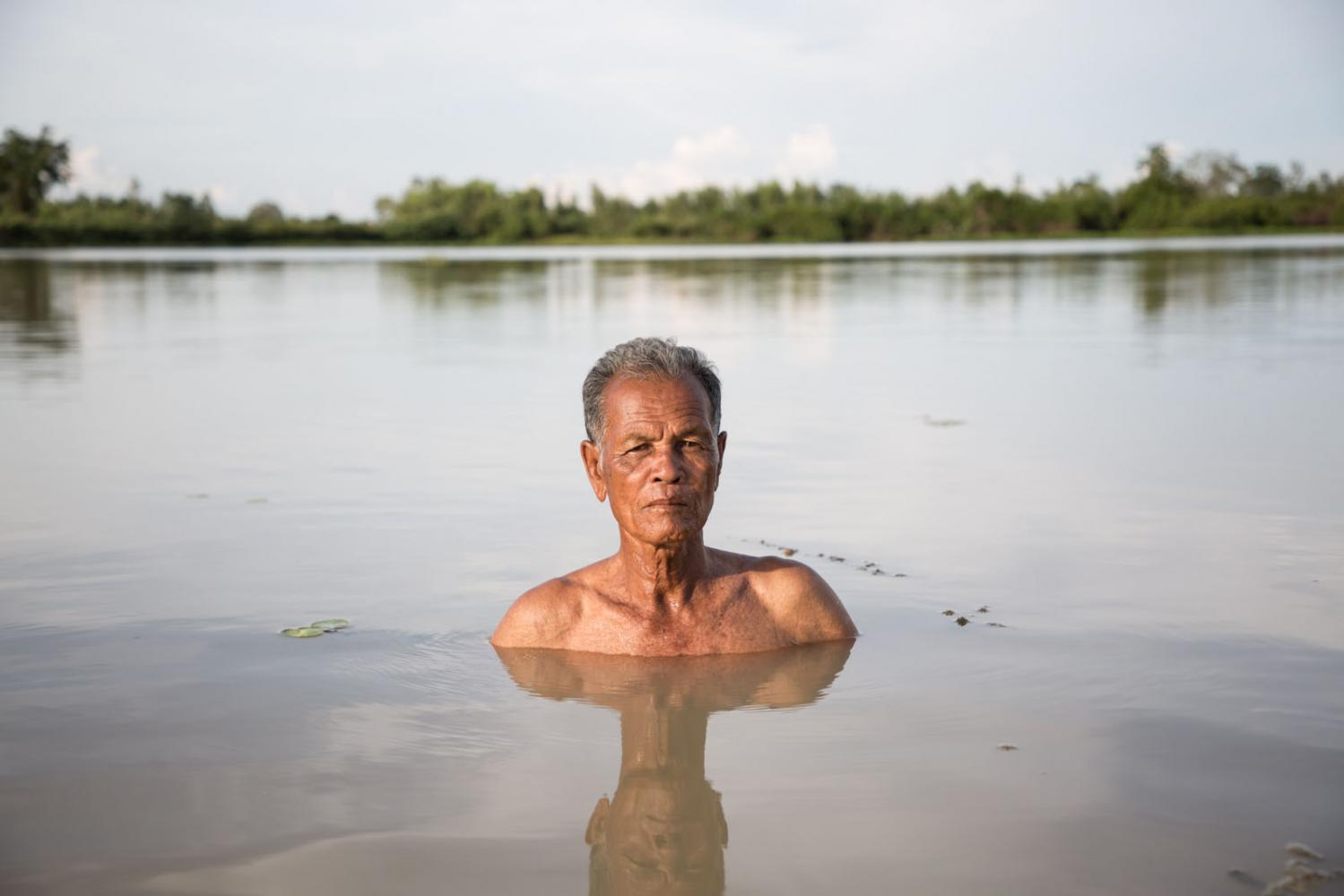 A man who's land was flooded by a dam constructed nearby stands in what was previously farmland. Si Saket, Thailand.
