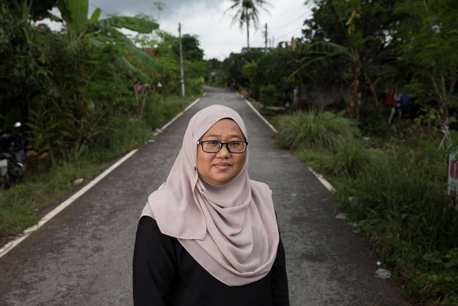 Women human rights defender Anchana Hemmina stands on a road in Pattani province, Thailand.