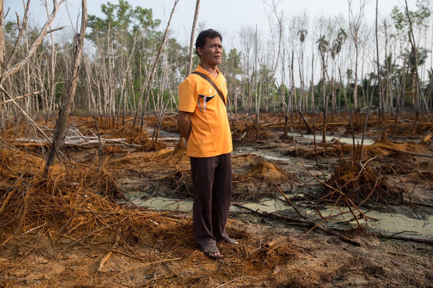 A villager stands on his neighbours polluted land caused by a recycling factory nearby. Rayong, Thailand.