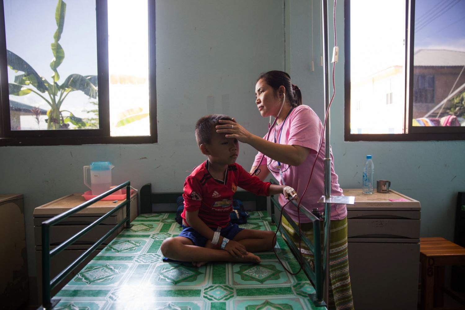 A nurse inspects a sick child brought to the Mae Tao clinic from inside Myanmar. Mae Sot, Thailand.
