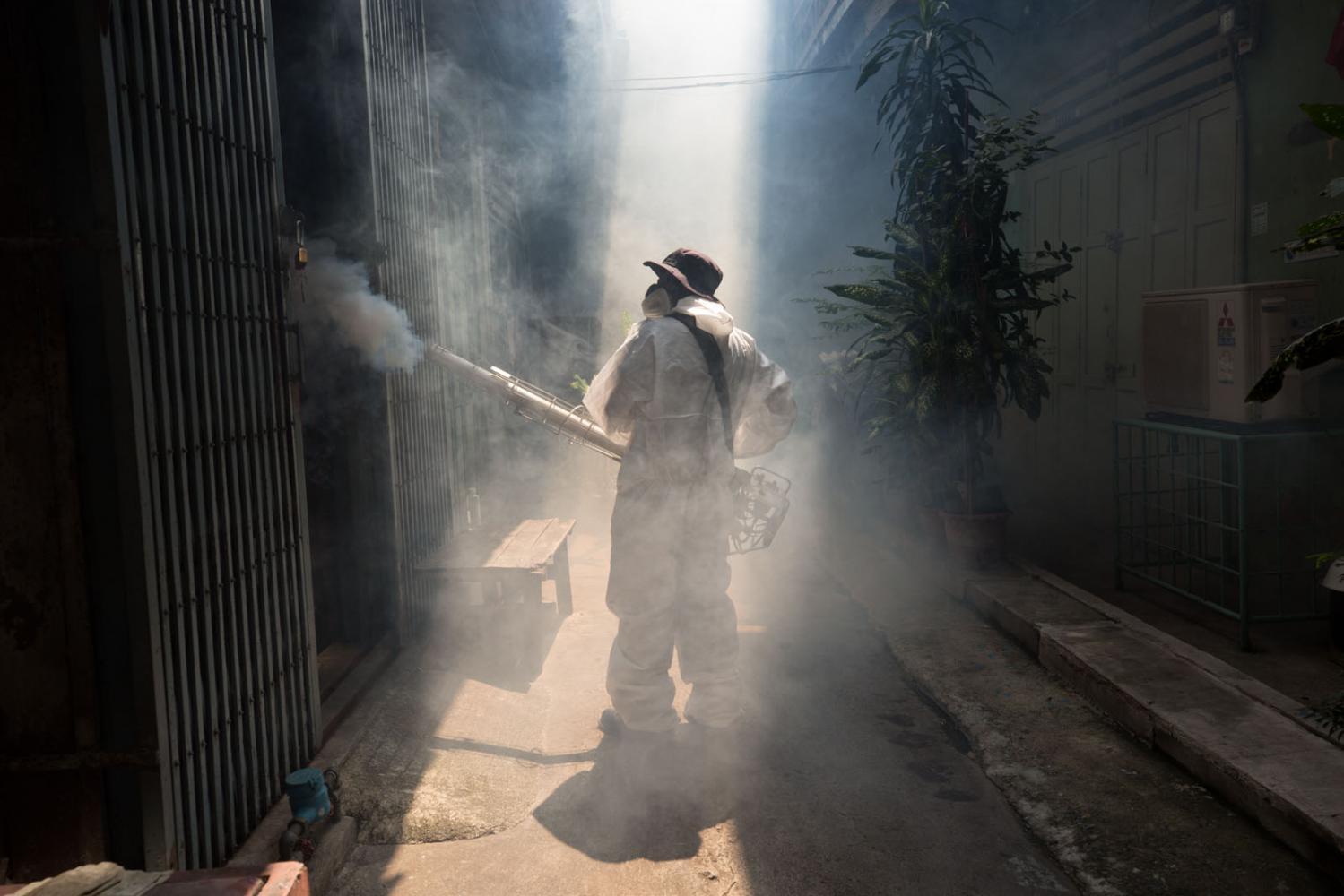 A worker from the Bangkok Metropolitan Administration (BMA) sprays a narrow street after a dengue fever outbreak. Bangkok, Thailand.