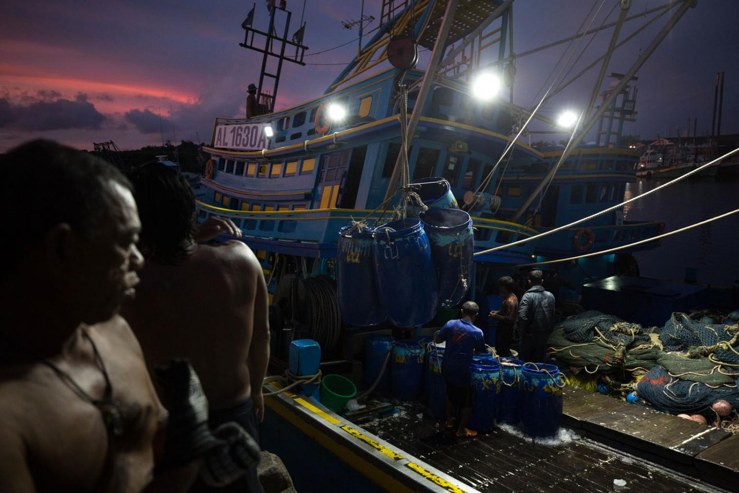 Trawler fishermen unload their catch at dawn. Phuket Harbour, Thailand.
