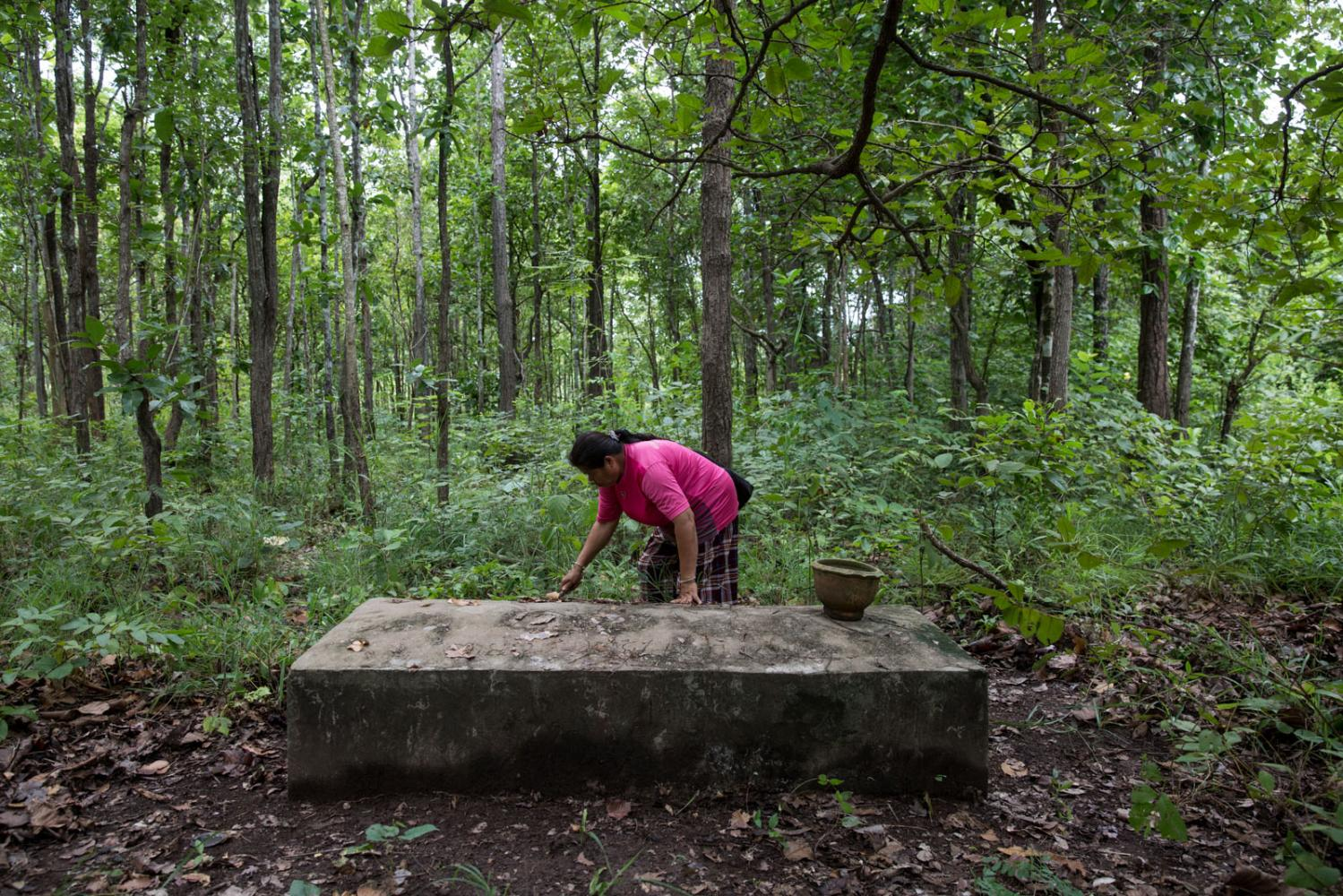 A women tidies the grave of her husband who was shot-dead by a gunman in the early 1990's during an on-going struggle against a stone mine. Nong Bua Lam Phu, Thailand.