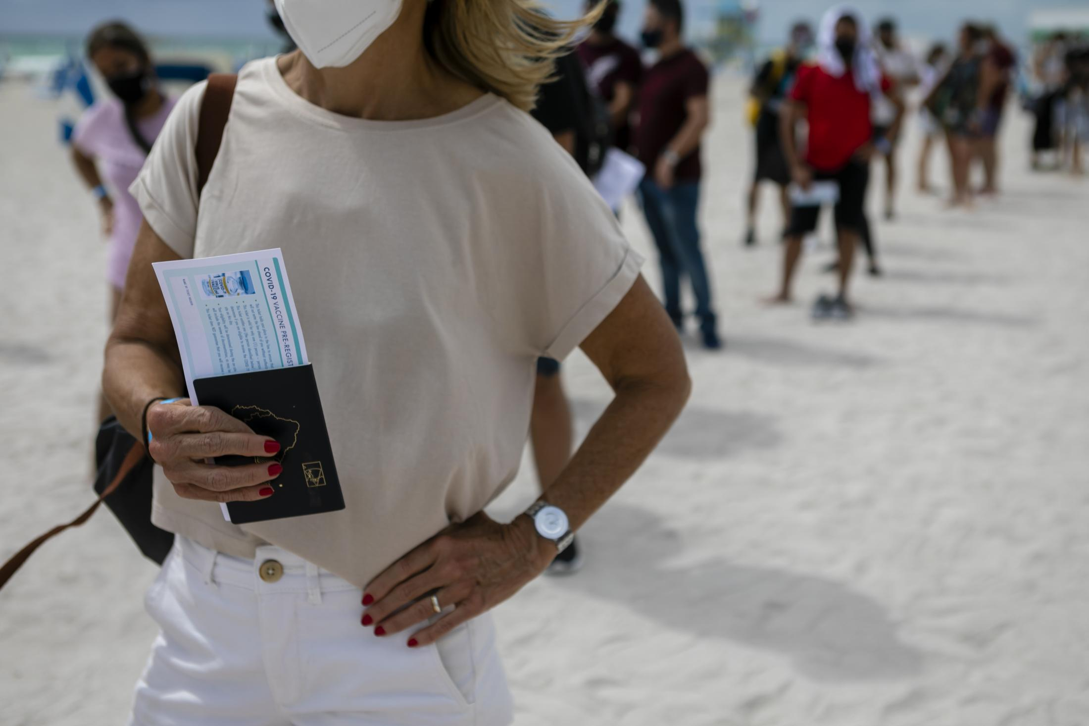 A woman holds her passport as she waits in line to get Johnson & Johnson COVID-19 vaccine at a pop-up vaccination center at the beach, in South Beach, Florida, on May 9, 2021. Eva Marie UZCATEGUI / AFP