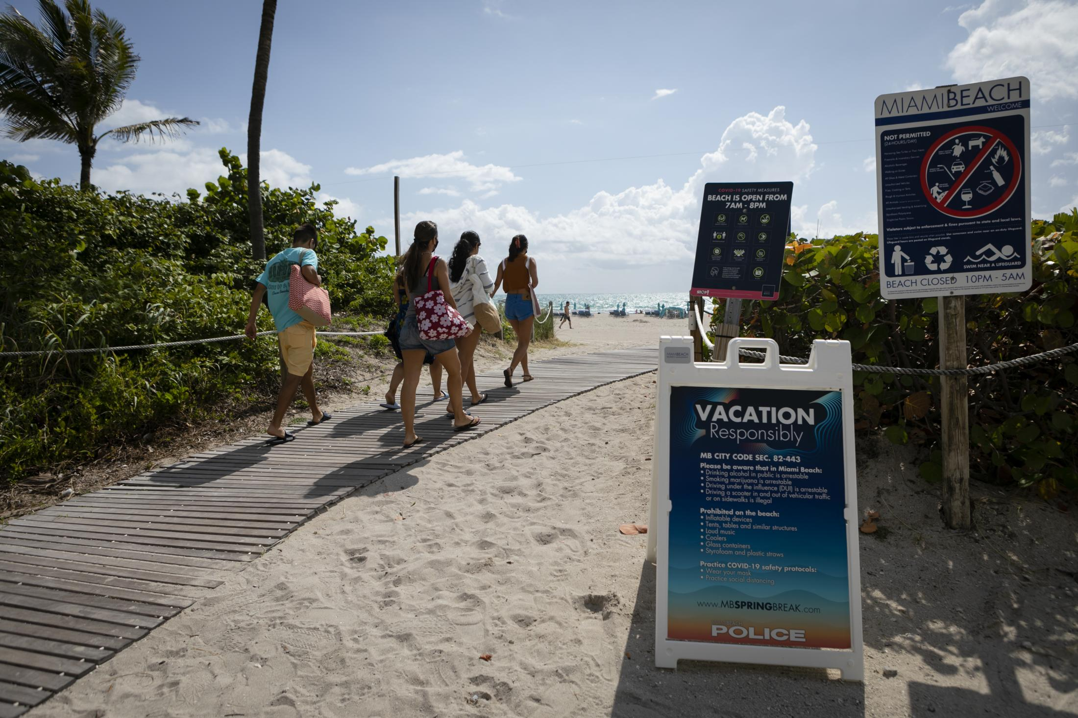 People pass by a sign center about Miami Beach rules at the beach, in South Beach, Florida, on May 9, 2021. Eva Marie UZCATEGUI / AFP