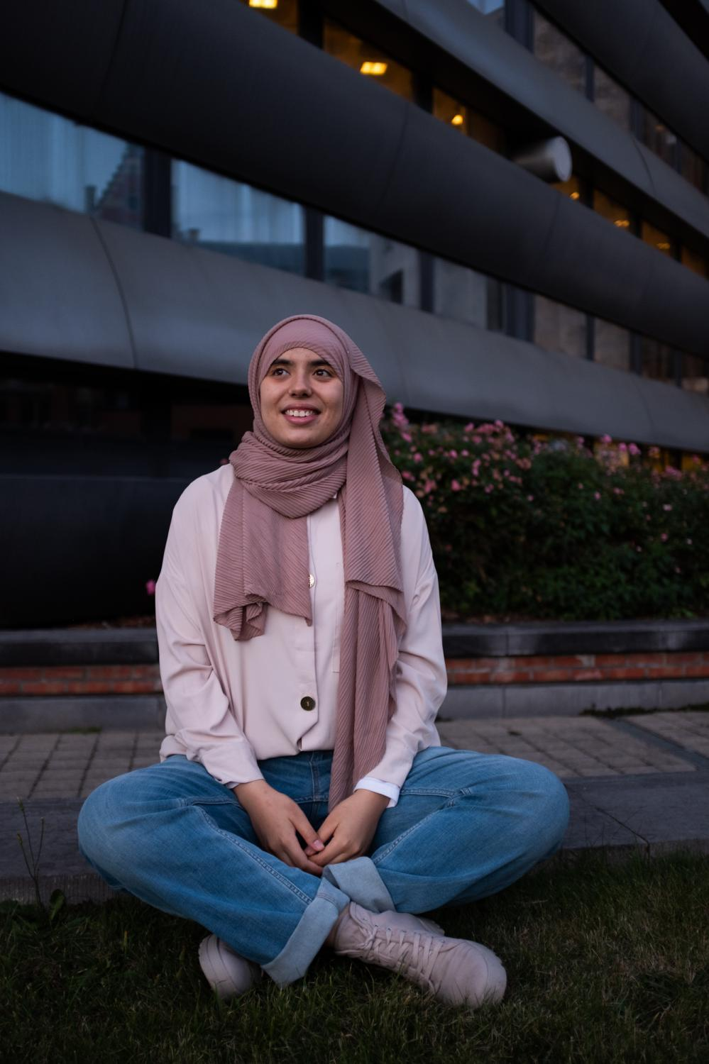 """""""Studies are what help me move forward, they are like a crutch, if I don't have access to them, my whole world collapses. I also feel that studying compensates for the fact that I am a foreign Muslim woman who wears a headscarf. I study to learn new skills to be useful for the society, but I'm sick of having to stress about my future internship, my future job, my future. """" Sarah El Harmoussi, 23, is in her final year of a master's degree in clinical psychology at ULB. She has always known that she wanted to study at university and she feels fulfilled in this faculty full of kindness and open-mindedness. But the hardest thing for Sarah was to find an internship that would accept her as she is. It took her a year to find an internship in an association after she passed an interview with her scarf. But one month later, her internship supervisor called her back to mention that she had forgotten to warn her that the veil was forbidden. Shocked, she decided not to let herself be defeated and launched an appeal on social networks. Thanks to this online solidarity, Sarah was able to find an internship at Médecins du Monde. """"I fight for the acceptance of everyone in their difference""""."""