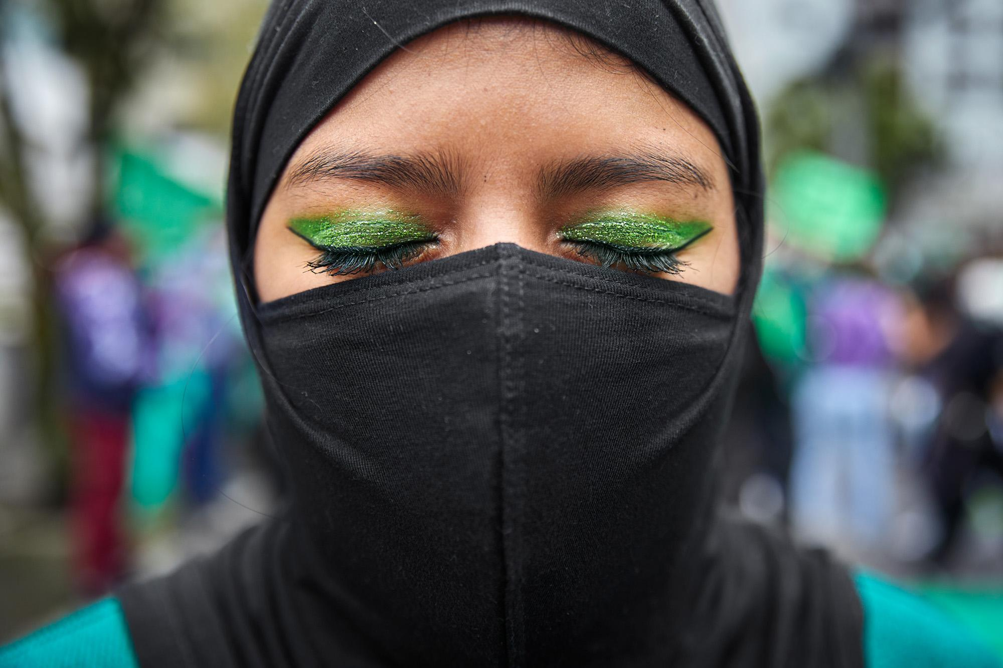 Portrait of a young woman, she has painted her eyes with green glitter. The color green has become a global symbol in the struggle for women's right to decide. April 28, 2021, Quito, Ecuador.