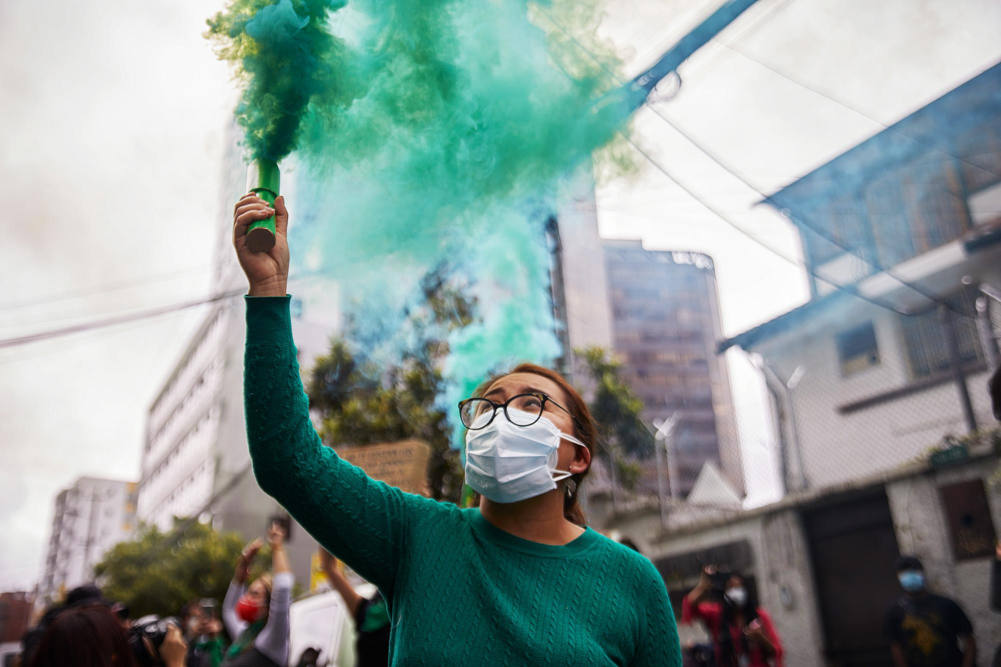 A woman holds a flare after the announcement of Ecuador's Constitutional Court ruling decriminalizing abortion in cases of rape of girls and women in the country. The color green has become a global symbol in the struggle for women's right to decide. April 28, 2021, Quito, Ecuador.