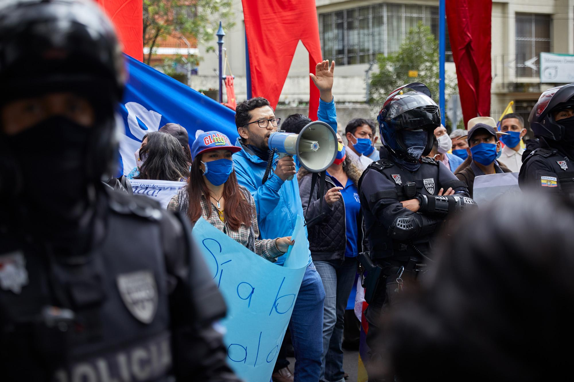 """Anti-rights groups, called """"pro-life"""", led mostly by men, are guarded by police as they pray and shout at feminist groups demanding decriminalization of abortion for rape. April 28, 2021, Quito, Ecuador."""