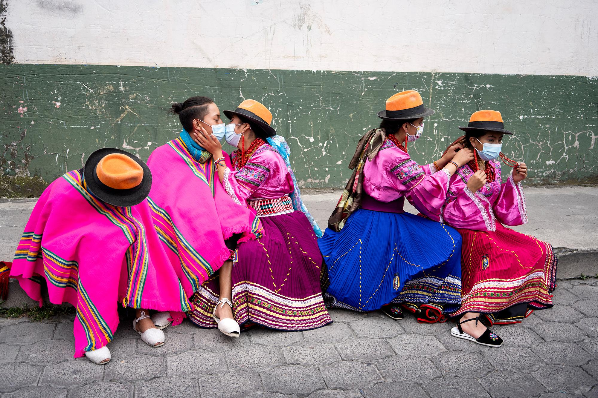"""Indigenous youth of the dance group """"Mashi Danza"""" rest after their participation in the National March for Democracy that arrived in Cotopaxi on the afternoon of February 22, 2021, demanding transparency in the electoral process of February 7th. Cotopaxi, Ecuador. Johis Alarcón for The New York Times."""