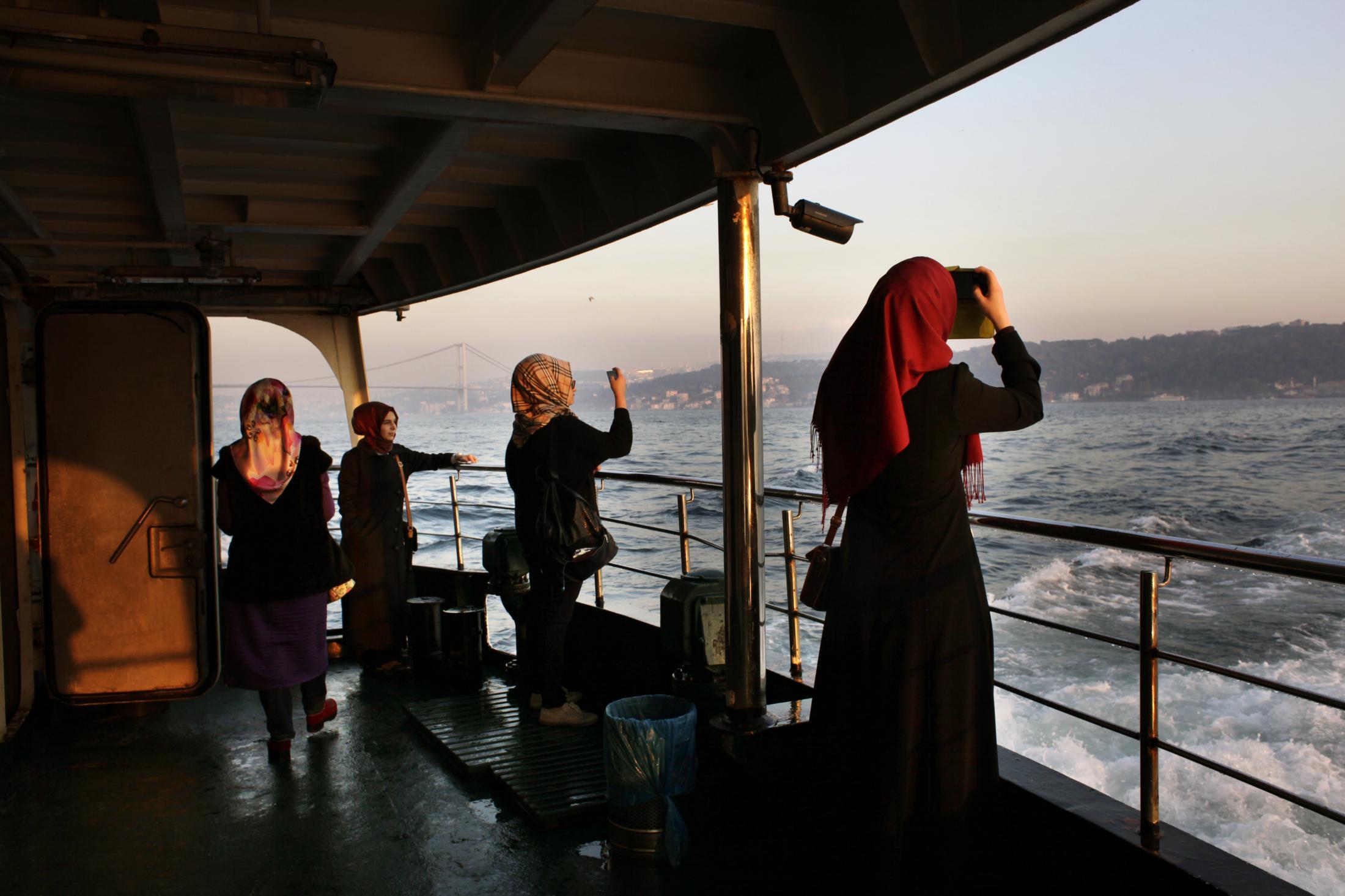 Turkish women are enjoying the sunset while taking a boat from the Asian side to the European side. Des femmes turques se prennent en photo pendant le coucher de soleil en prenant le bateau de la rive asiatique à la rive européenne