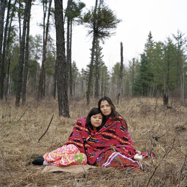 """Dannataya, 10 at the time, and her aunt Michelle Burns, 30 at the time, find peace among the trees in Prince Albert, Saskatchewan. Monica Lee Burns, Dannataya's mother and Michelle's twin sister, was murdered by a stranger, 38-year-old white male Todd Daniel McKeaveney, and found dead in a desolate area outside Prince Albert in January 2015. McKeaveney received 13 years in prison. """"I feel lonesome a lot. My Elder tells me to pray to the Creator and to go near a tree,"""" Michelle said. """"When you think about all the missing and murdered indigenous women, they don't have a voice, so their family members are the ones trying to have a voice. I have to remember that [Dannataya] is watching me. When I walk, I try to walk with good intentions so that when she's older she won't end up lost. Her mom would want good things for her."""" Copyright © Sara Hylton/Redux Picutres, 2017"""