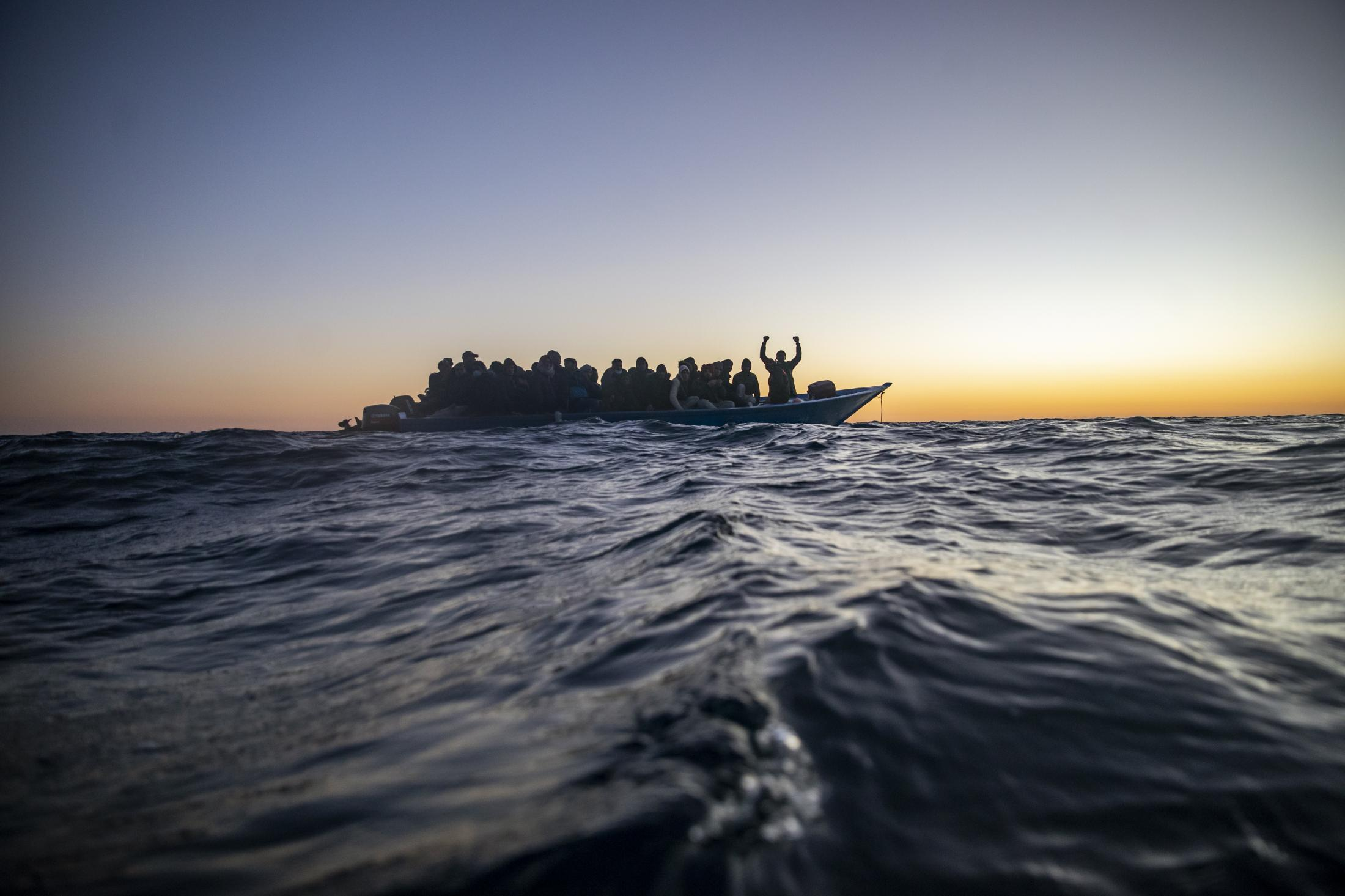 Migrants and refugees from different African nationalities wait for assistance aboard an overcrowded wooden boat, as aid workers of the Spanish NGO Open Arms approach them in the Mediterranean Sea, international waters, at 122 miles off the Libyan coast, Friday, Feb. 12, 2021.