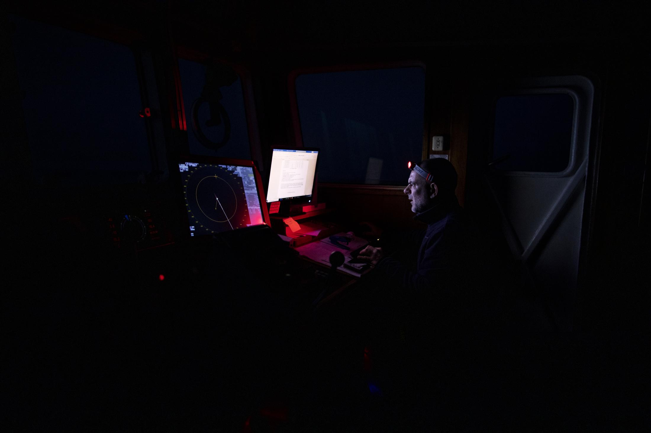 49-year-old 'Erri' from Bilbao, Chief Mate of the Spanish NGO Open Arms during a watch a few hours before dawn analyses the latest data on the ship's position and direction, Saturday Feb.6,2021