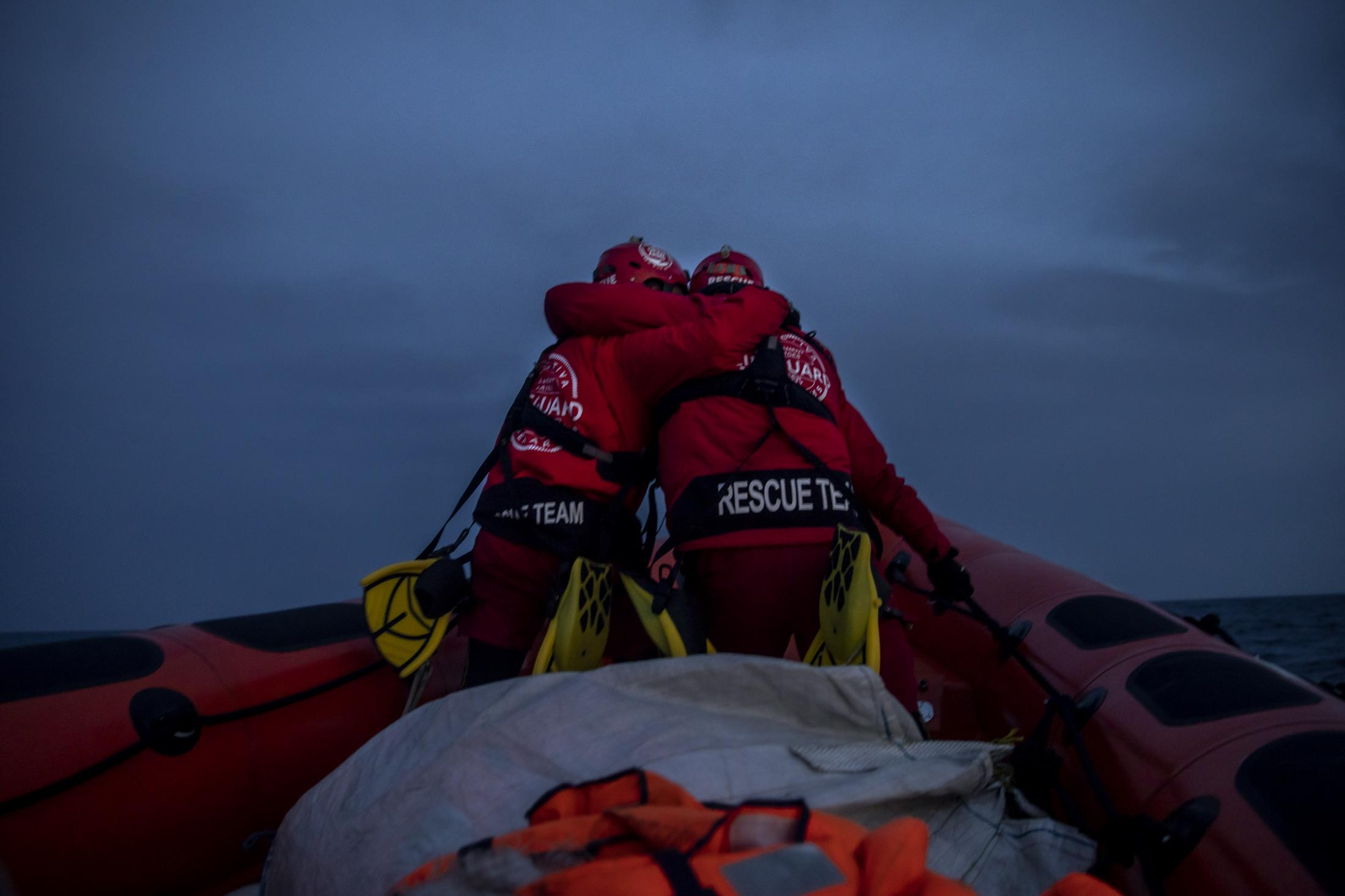 Rescuers of the Spanish NGO Open Arms, Alberto Agrelo and Alejandro Samper embrace in a gesture of encouragement as they go to a possible target, Saturday,Feb.6,2021