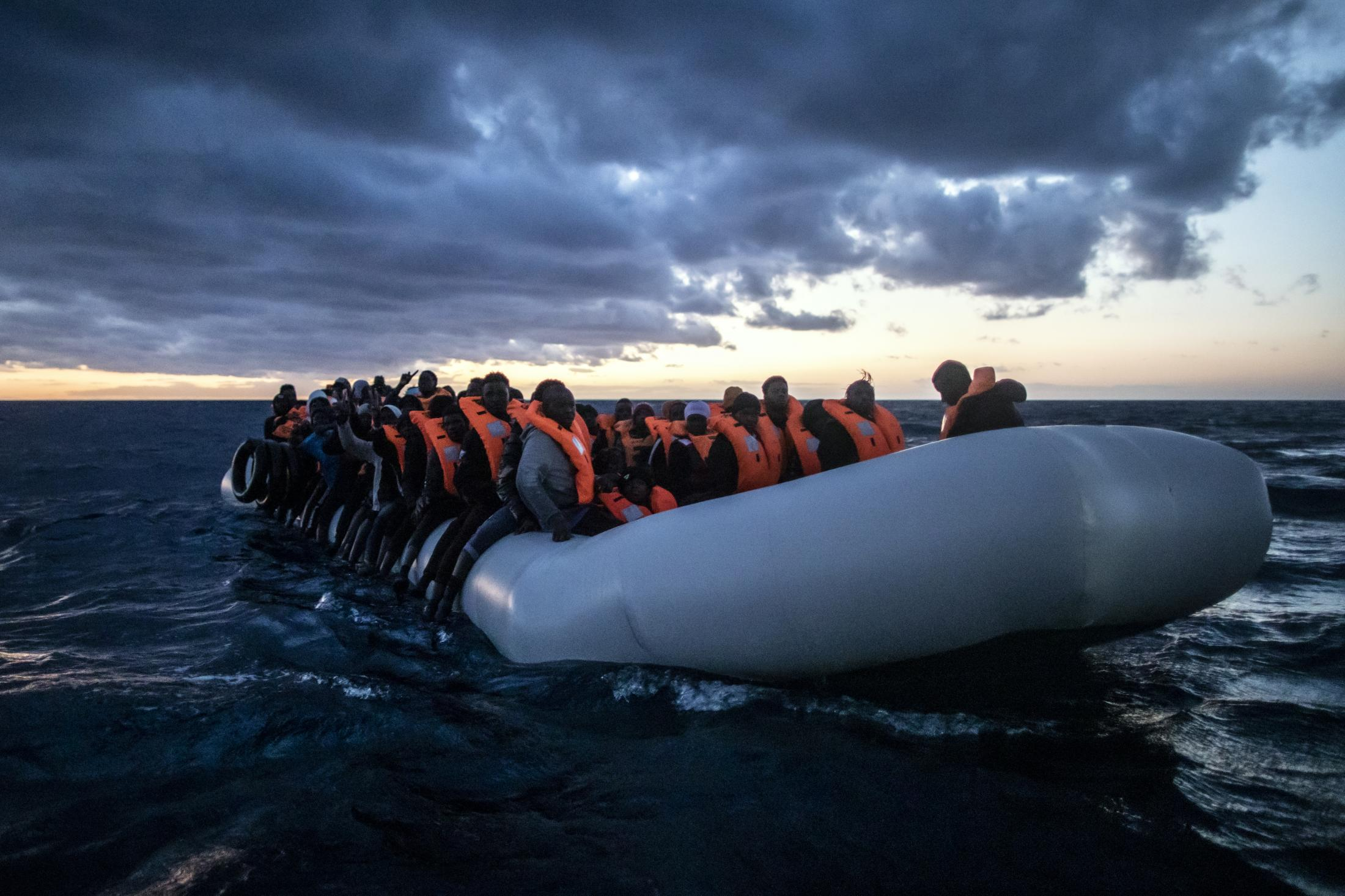 Migrants and refugees from different African nationalities wait for assistance aboard an overcrowded rubber boat, as aid workers of the Spanish NGO Open Arms approach them in the Mediterranean Sea, international waters, at 80 miles off the Libyan coast, Saturday Feb. 13, 2021.