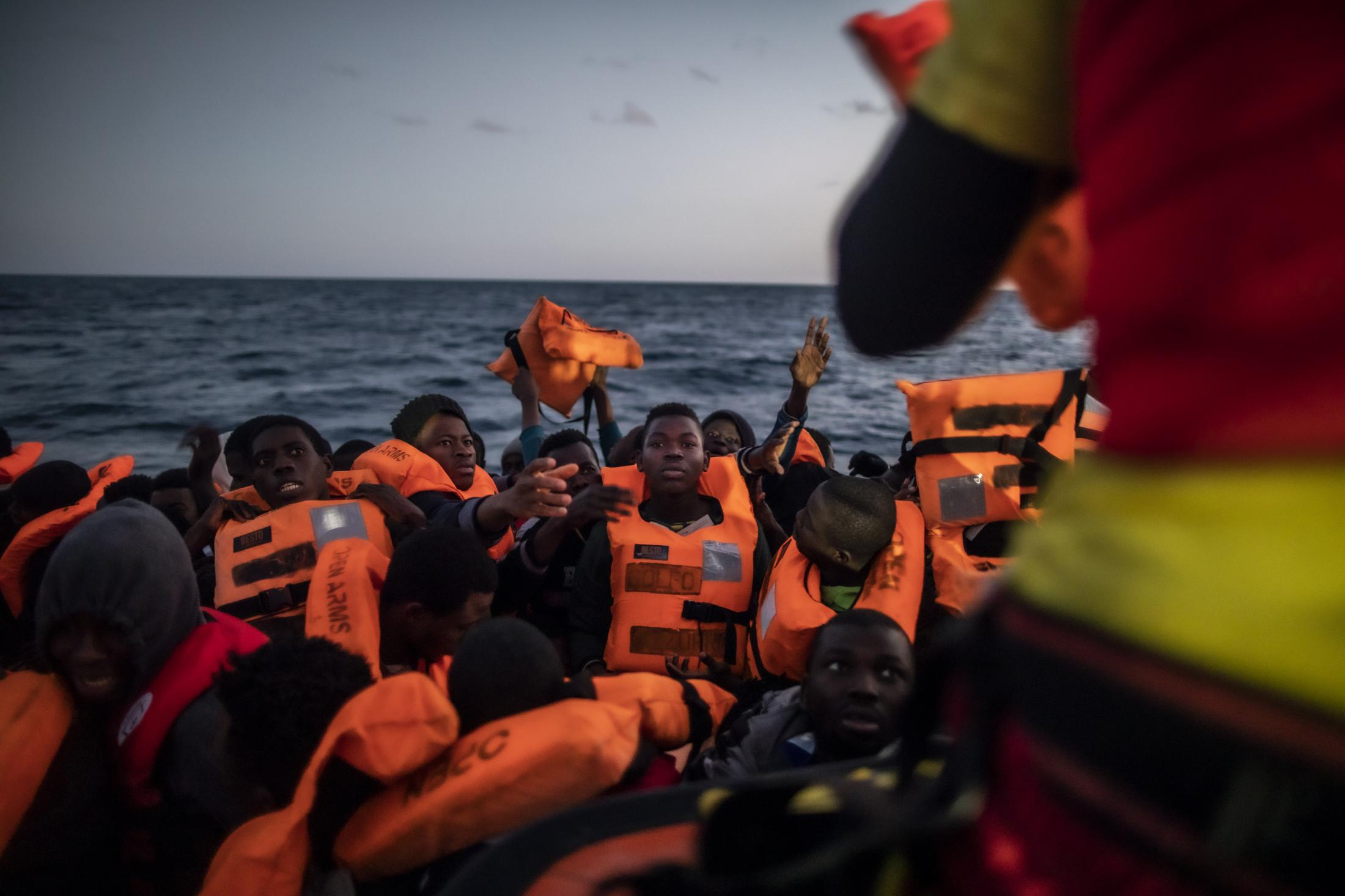 Rescuer Alberto Agrelo distributes the waistcoats to all the migrants, in the centre of the picture, Bamba Bourahima, 14 years old from Ivory Coast Migrants and refugees from different African nationalities wait for assistance aboard an overcrowded rubber boat, as aid workers of the Spanish NGO Open Arms approach them in the Mediterranean Sea, international waters, at 80 miles off the Libyan coast, Saturday Feb. 13, 2021.