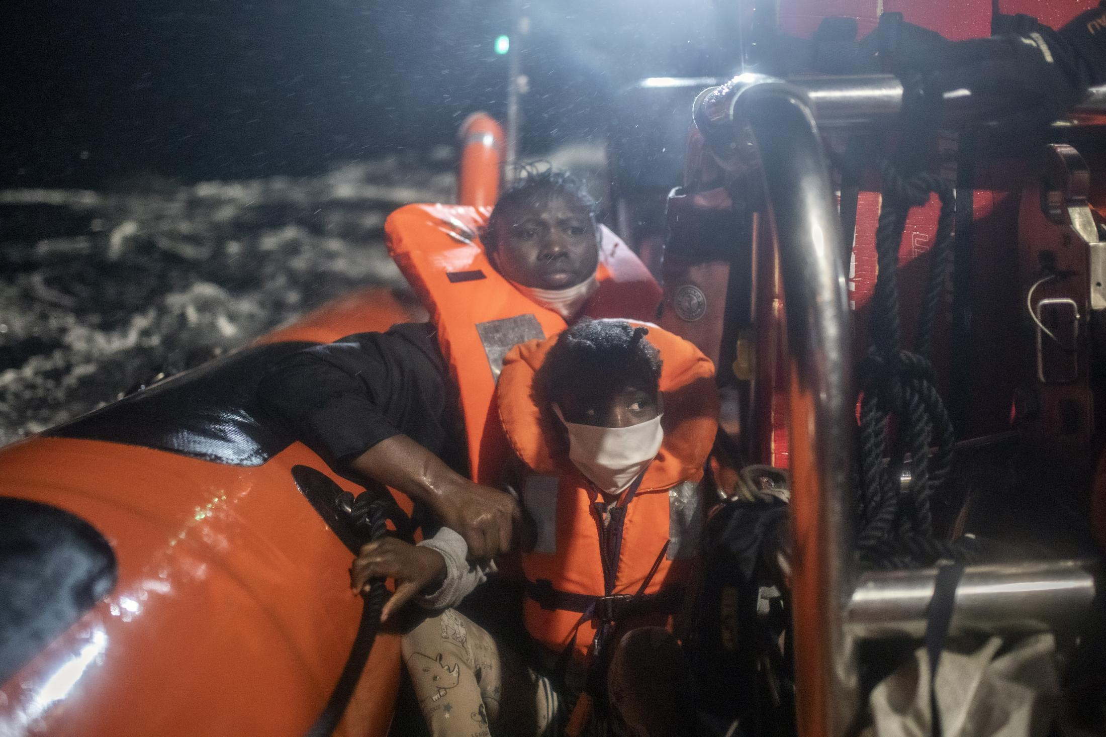 25-year-old Santa, originally from the Ivory Coast, can be seen clutching her 5-year-old daughter Timi's arm to prevent her from falling into the water, after being rescued from an overcrowded rubber boat Saturday, Feb. 13, 2021,