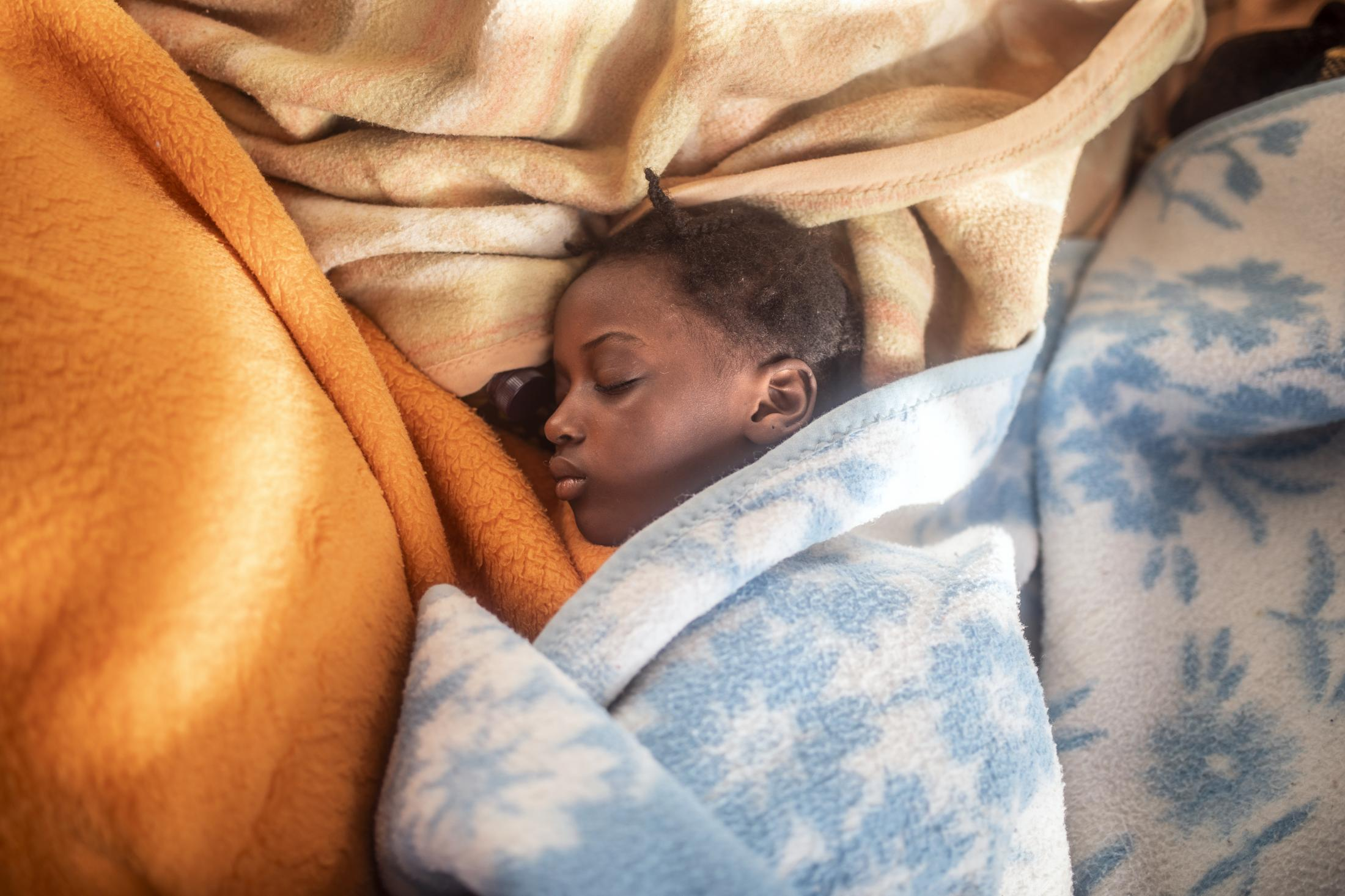 5 year old Timi sleeps between the blankets at her mother's feet, basking in the warmth of the sun's rays after been rescue by the Spanish NGO Open Arms Sunday, Feb. 14, 2021