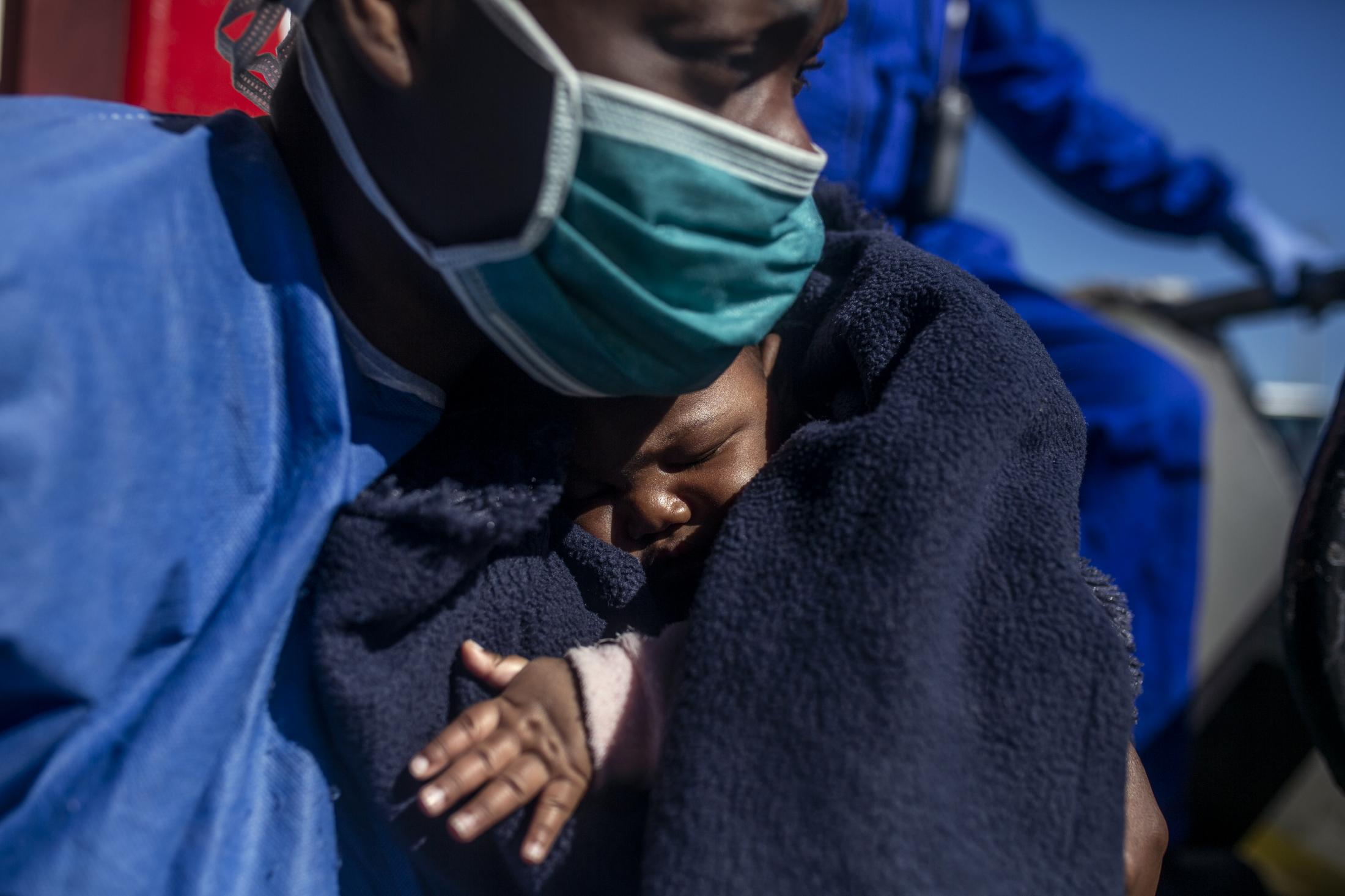 Sandrine,33 years old, Cameroon, holds her three-month-old son Moise moments before leaving the Spanish NGO Open Arms boat, in the Sicilian port of Empedocles, Italy, Tuesday, Feb. 16, 2021