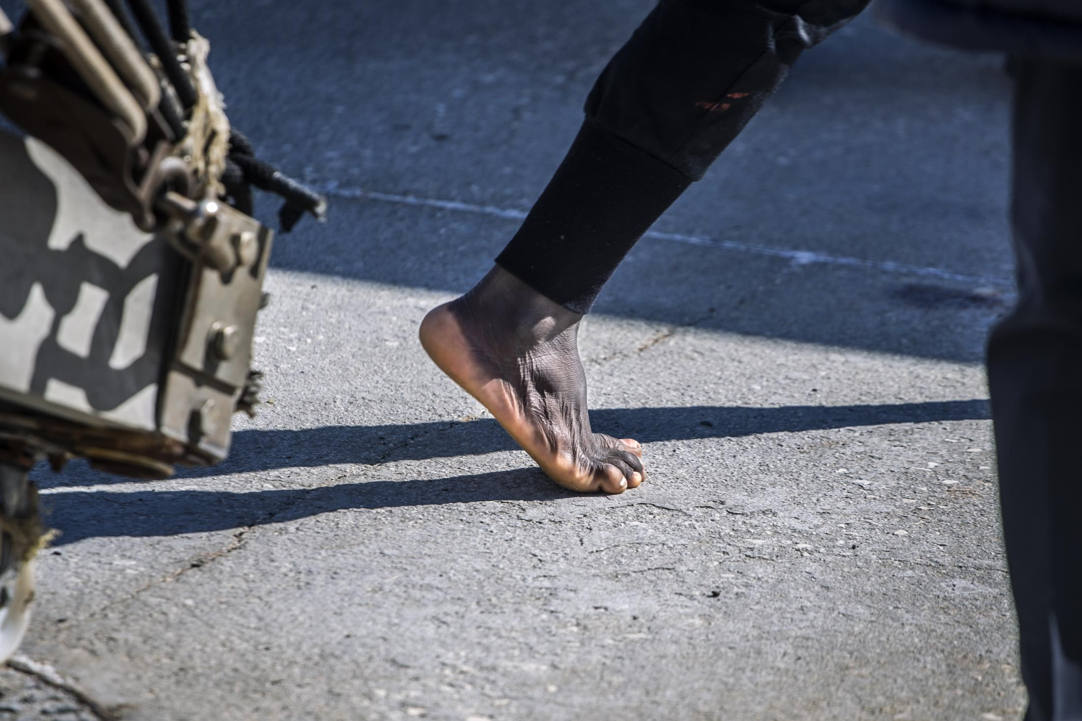 A migrant steps on the ground barefoot in the Italian port of Empedocles after being rescued by the Spanish NGO Open Arms in the Central Mediterranean Sea, Tuesday, Feb 16, 2021