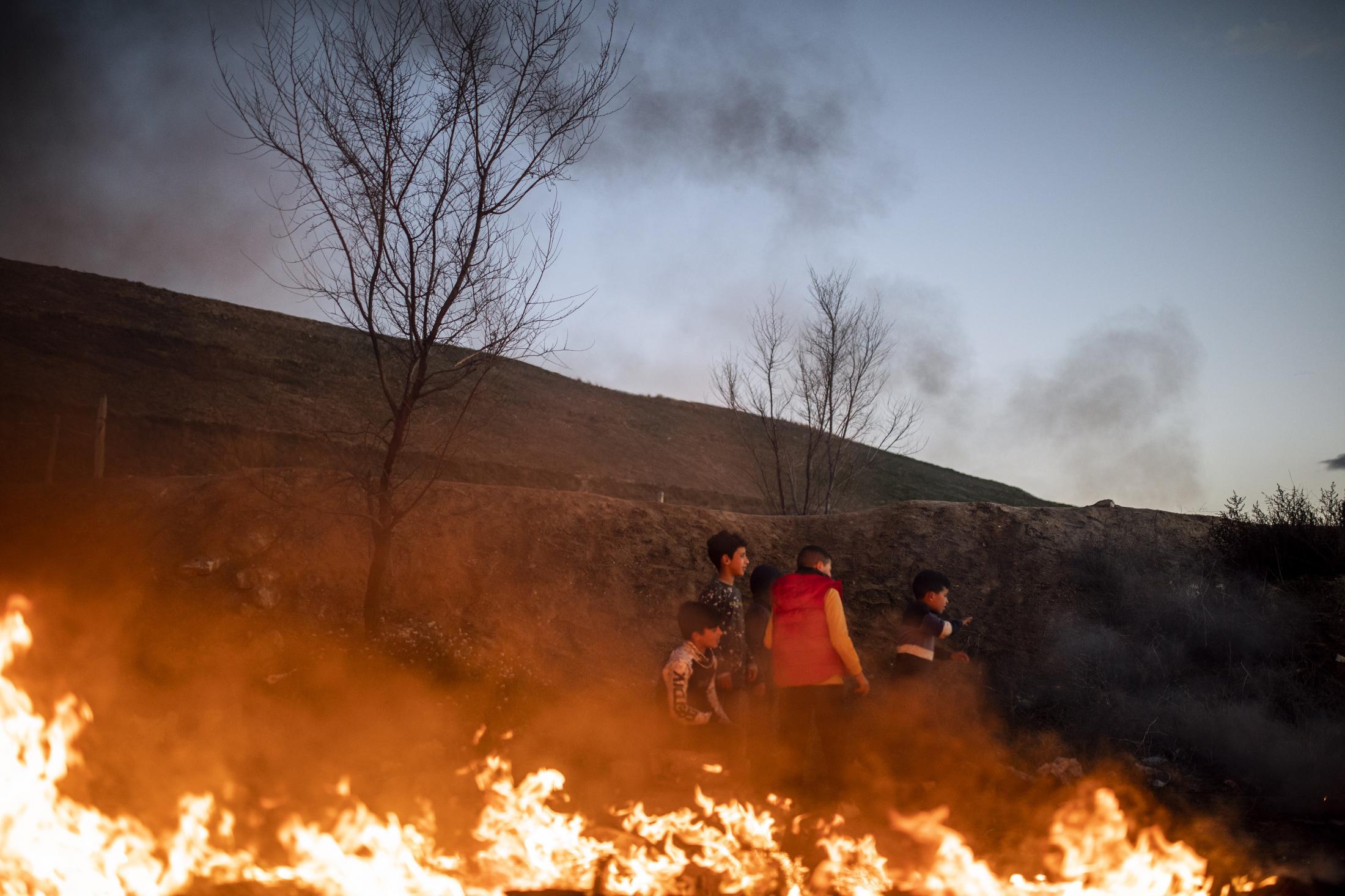 Varios ni–os juegan alrededor del fuego para poder calentarse en el Sector VI de la Ca–ada Real