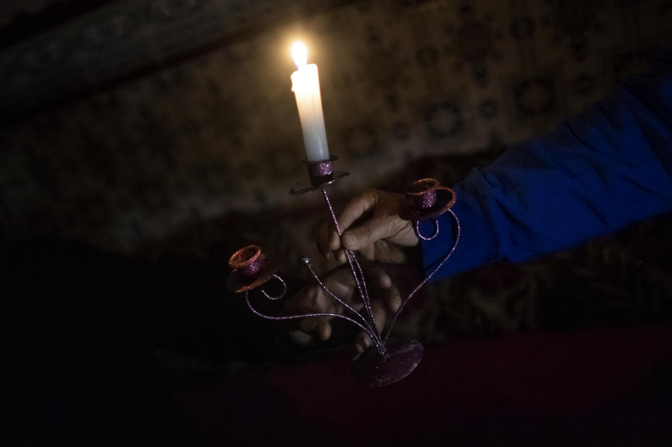 Naima le entrega a su marido Abdel-Asis una vela para poder iluminar dentro de su hogar situado en el Sector V de la Cañada Real