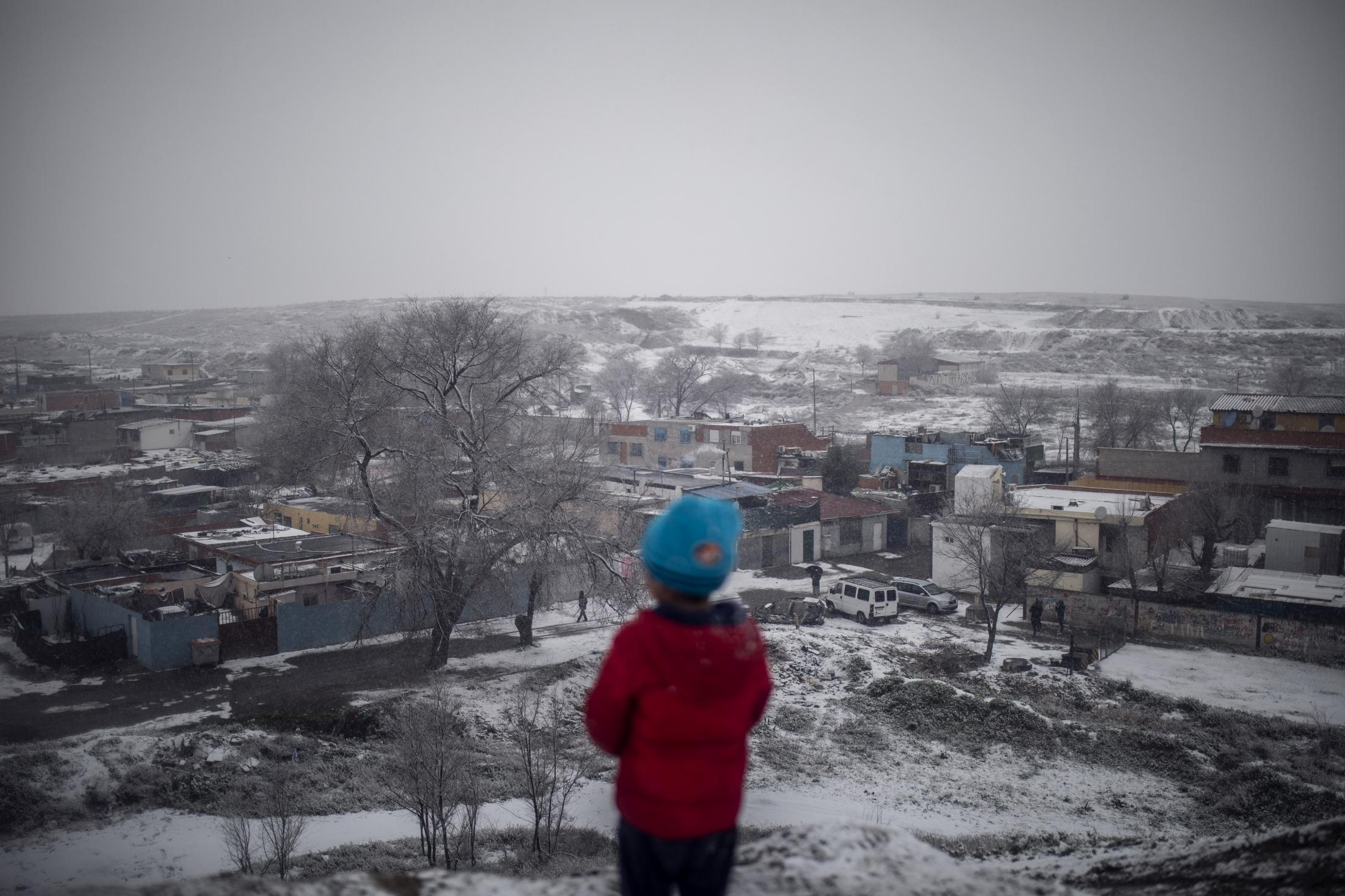 Un niño observa desde lo alto de una ladera el Sector VI de la Cañada Real durante la nevada