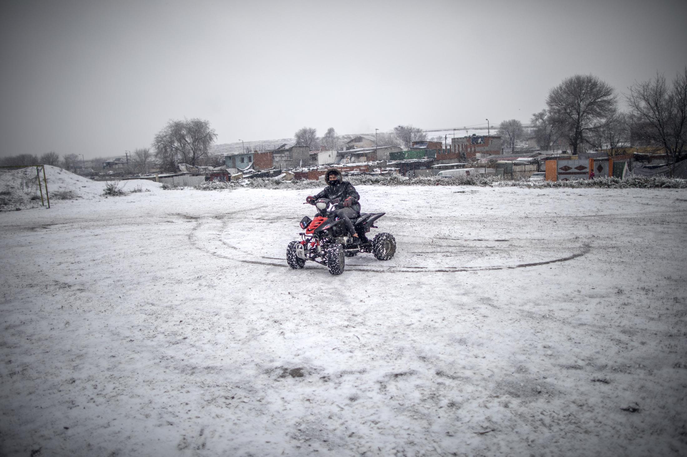 Un joven usa su quad en el campo de futbol lleno de nieve en el Sector VI de la Ca–ada Real