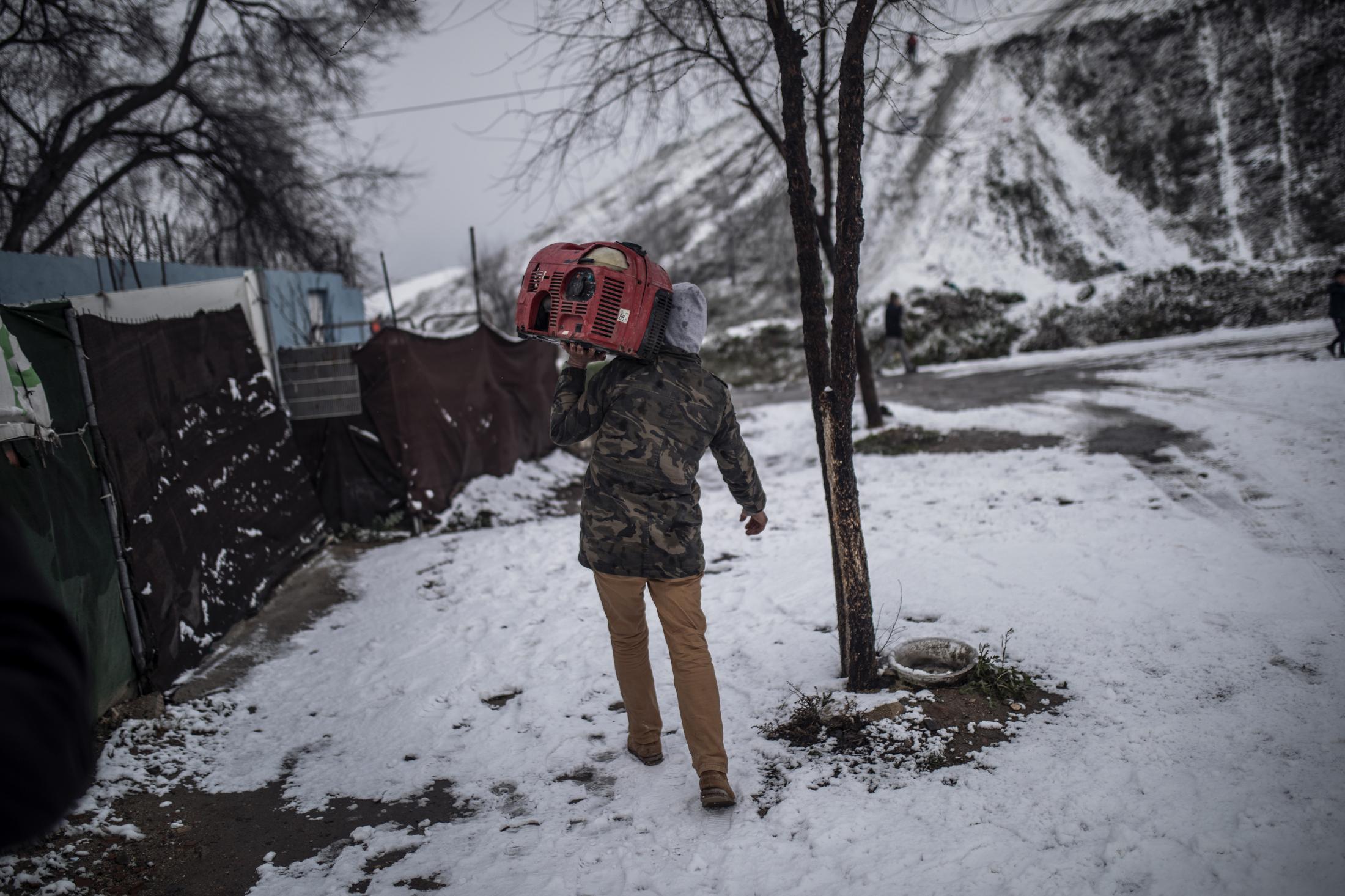 Un hombre carga a hombros un generador a gasolina para poder usarlo en tener algo de electricidad en su hogar en el Sector VI de la Ca–ada Real