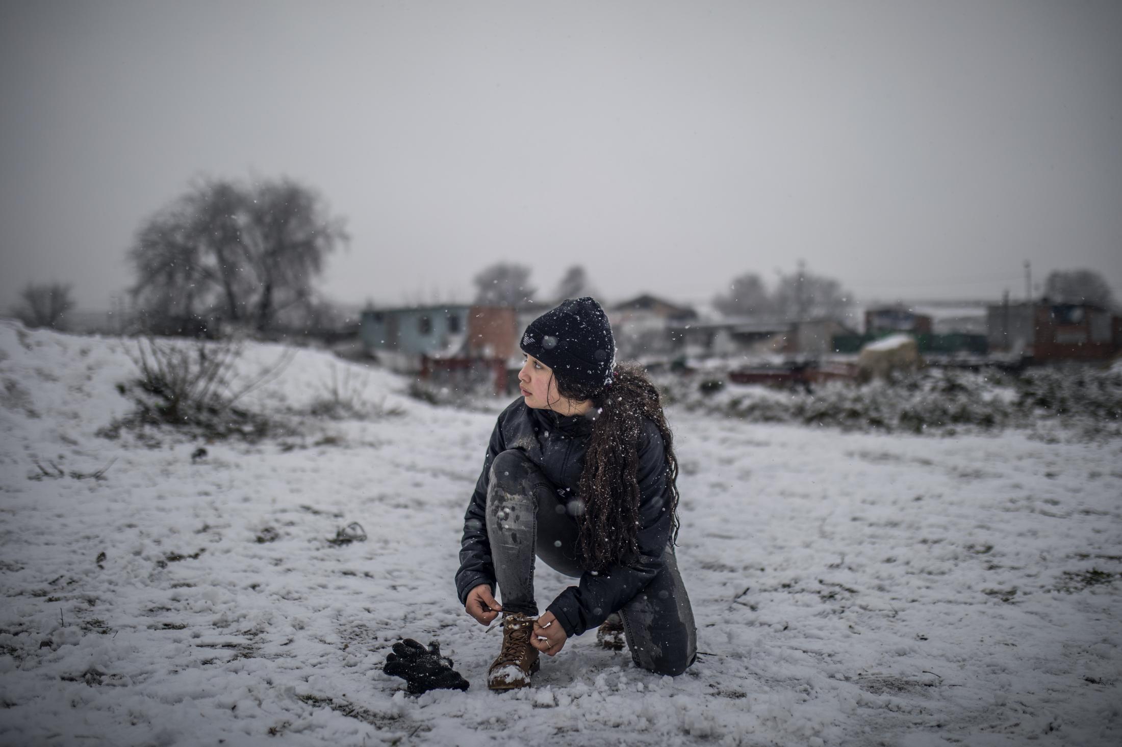 Una ni–a se ata los cordones mientras juega con sus amigos en la nieve en el Sector VI de la Ca–ada Real