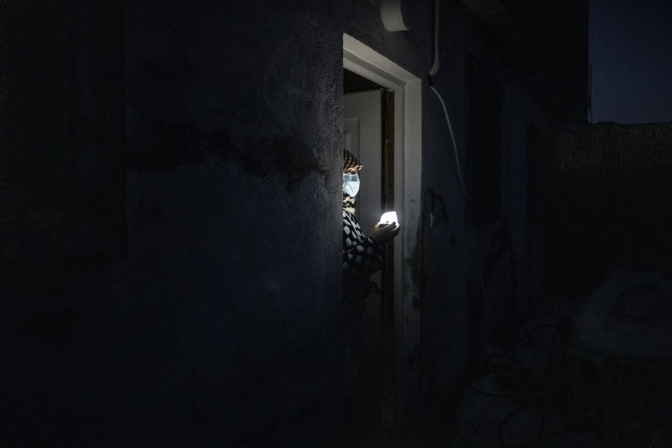 Naima sujeta una lampara elŽctrica a la puerta de sus casa en el Sector V de la Ca–ada Real