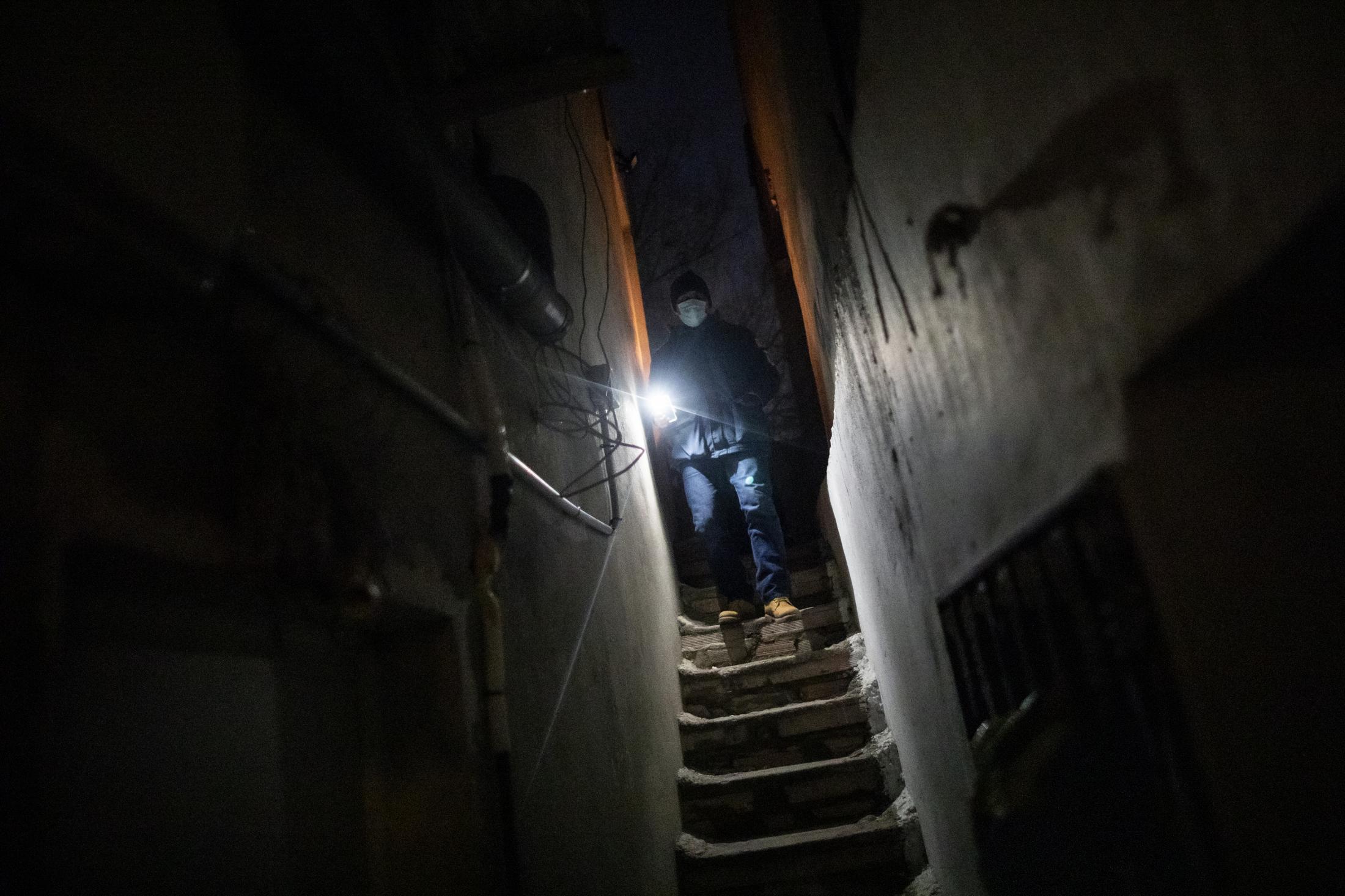 Omar baja las escaleras hacia su casa en el Sector V con el m—vil encendido para poder iluminarse