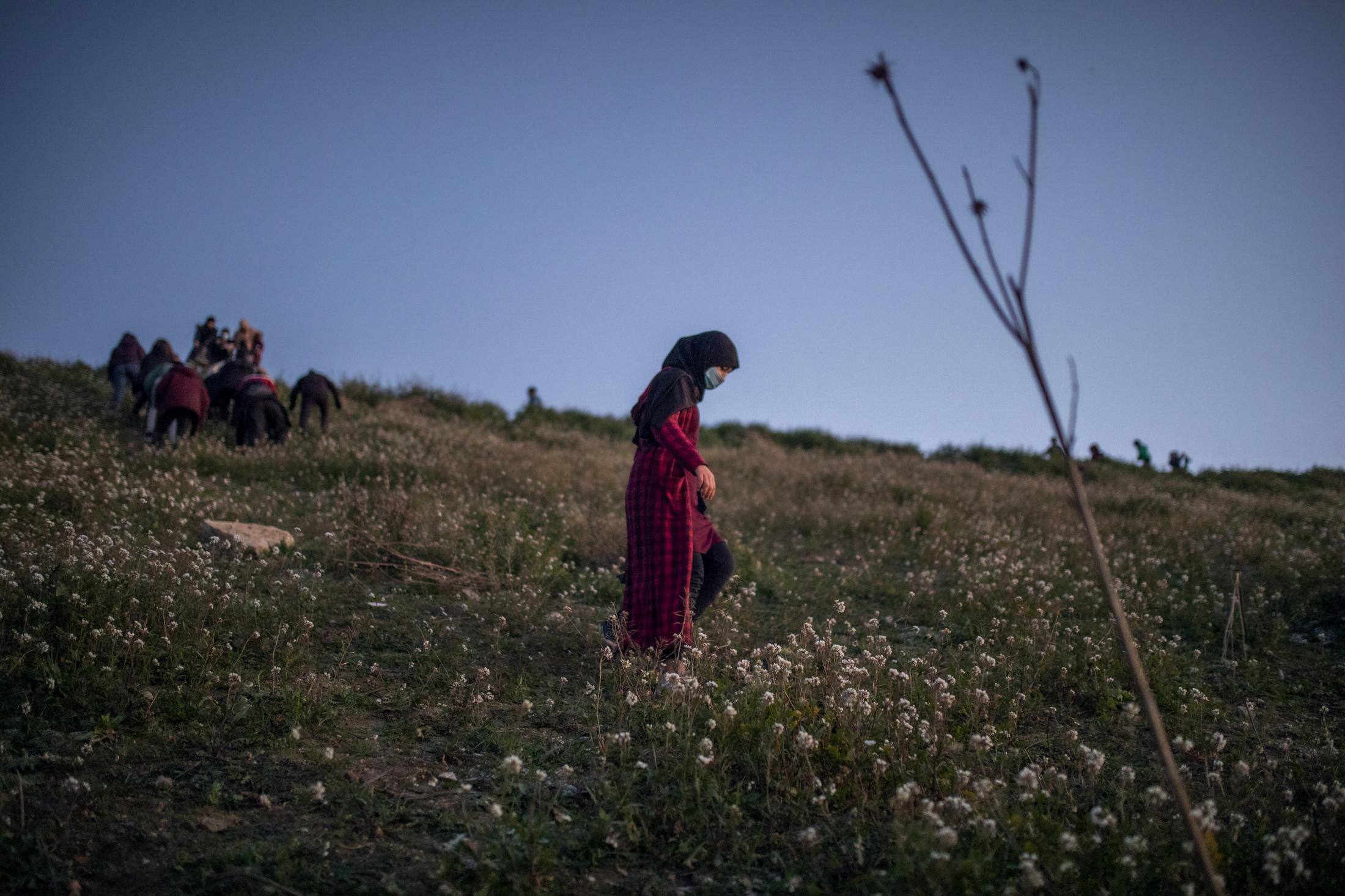 Una mujer intenta subir la colina de la mano de su hijo para poder ver las vistas desde lo alto en el Sector VI de la Cañada Real