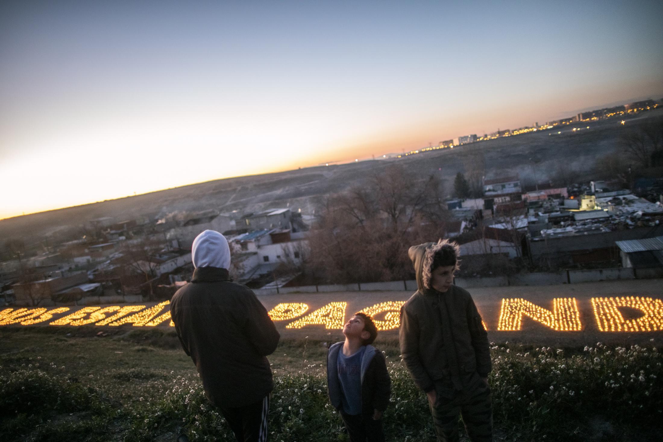 Tres j—venes ven desde lo alto de la colina del Sector VI las velas donde se lee: 'Nos est‡n apagando' . Una acci—n realizada conjuntamente por la asociaci—n de mujeres Tabadol y el grupo de artistas Boa Mistura