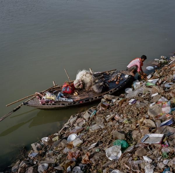 Babu Sahni, 30 at the time, and his son Himanshu Kumar Sahni, 8 at the time, fish along a bank scattered with waste on the Punpun river, a tributary of the Ganges in Fatuha, Bihar. Copyright © Sara Hylton/National Geographic, 2019