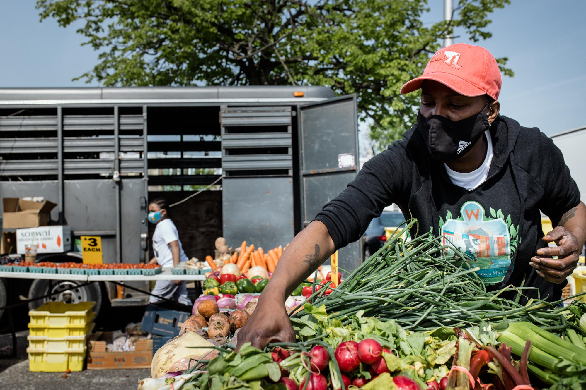 BALTIMORE, MD - APRIL 24, 2021: Cassandra Harris organizes vegetables from Pine Grove Farm at the Waverly Farmers Market, one of the few year round markets, in Baltimore, Maryland on April 24, 2021. Last year, there were fewer customers because of the COVID-19 pandemic.