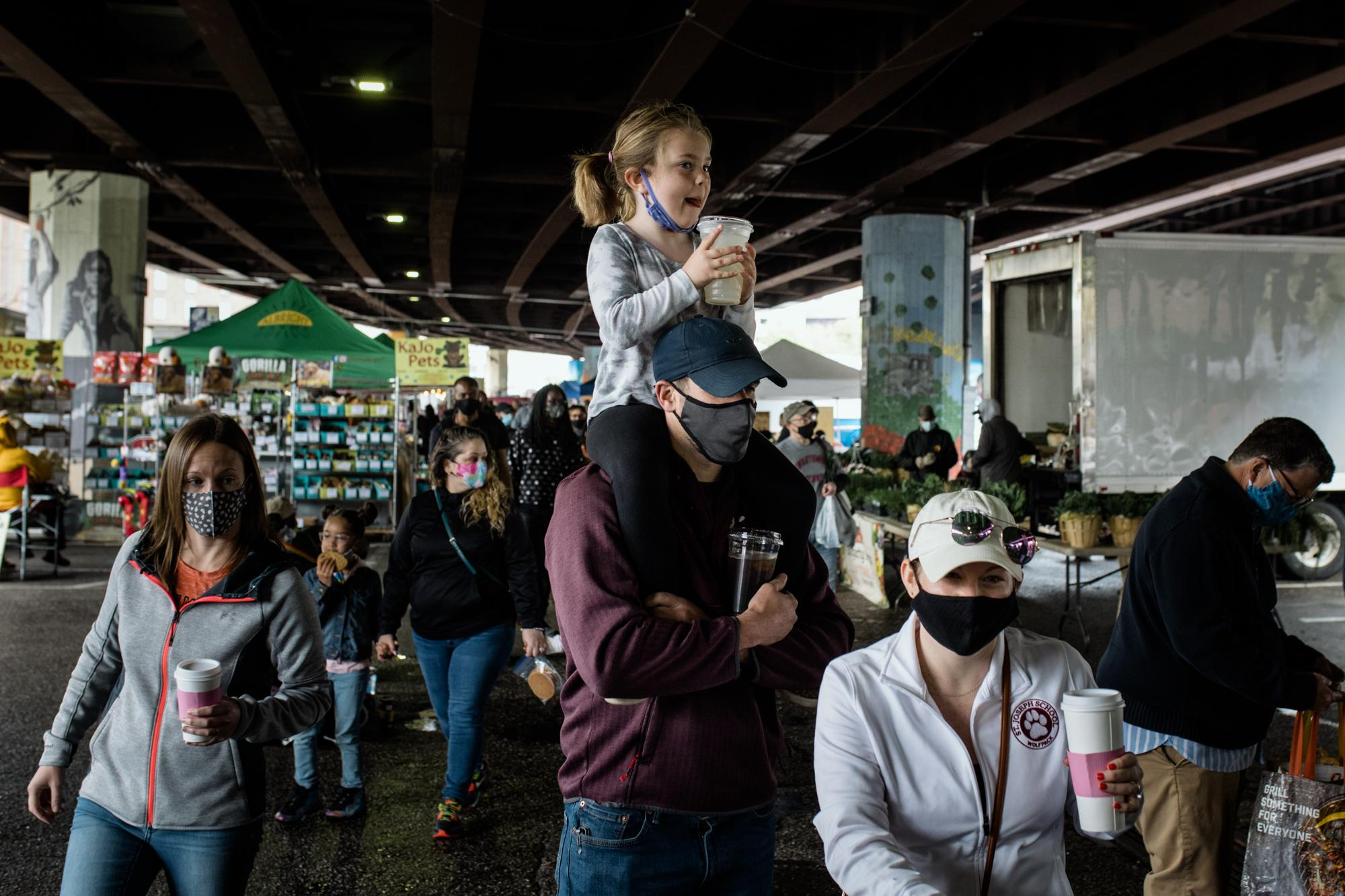 BALTIMORE, MD - APRIL 25, 2021: Shoppers visit the Baltimore Farmers Market & Bazaar under the Jones Falls Expressway Bridge in Baltimore, Maryland on April 25, 2021. Last year, the farmer's market opened two months later than usual, with limited numbers of vendors. Customers were allowed in one at a time. This year, the farmer's market reopened in April for the season without any restrictions.