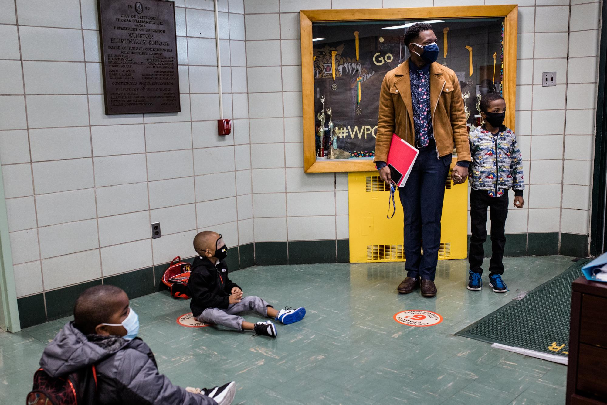BALTIMORE, MD - NOVEMBER 16, 2020: Principal Brandon Pinkney guides his students, (L-R), James Jennifer, Evan Gillard and Tayvon? on the new safety procedures to have in-person classes for the first time since the start of the coronavirus pandemic at Walter P Carter Elementary/Middle school.