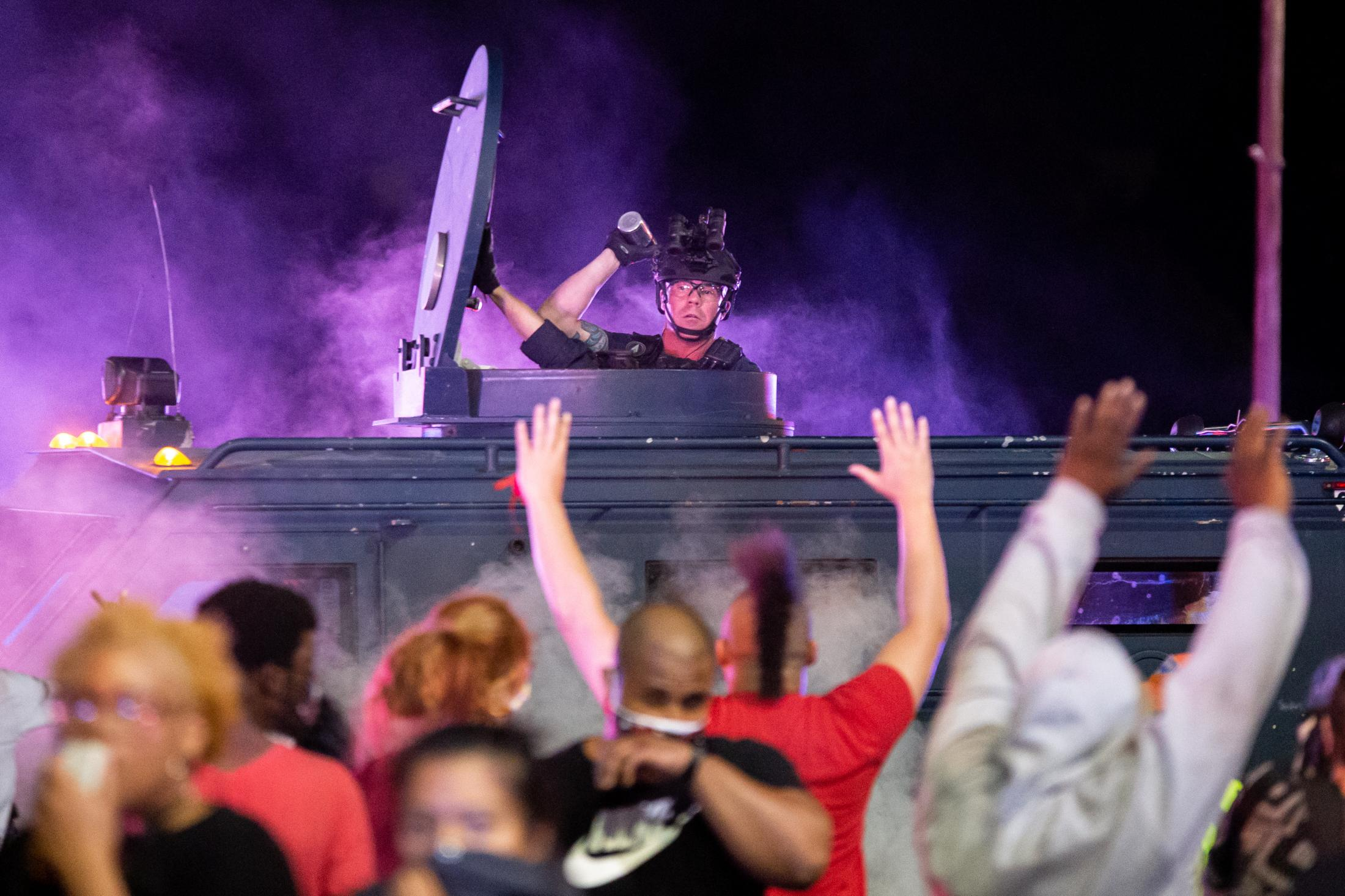 A Dallas Police officer opened the top hatch of the armored vehicle and threw multiple grenades of tear gas at the crowd of protestors.
