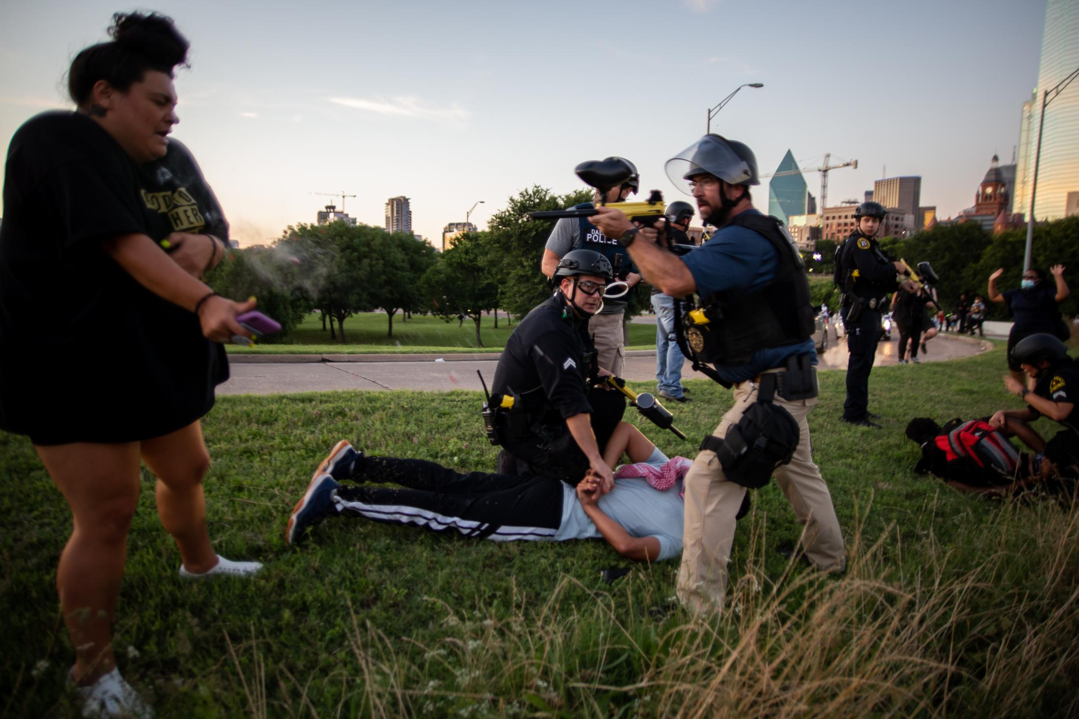 A Dallas Police Officer shoots pepper balls at a peaceful protester in close range, the woman was arrested and booked in Dallas County Jail.