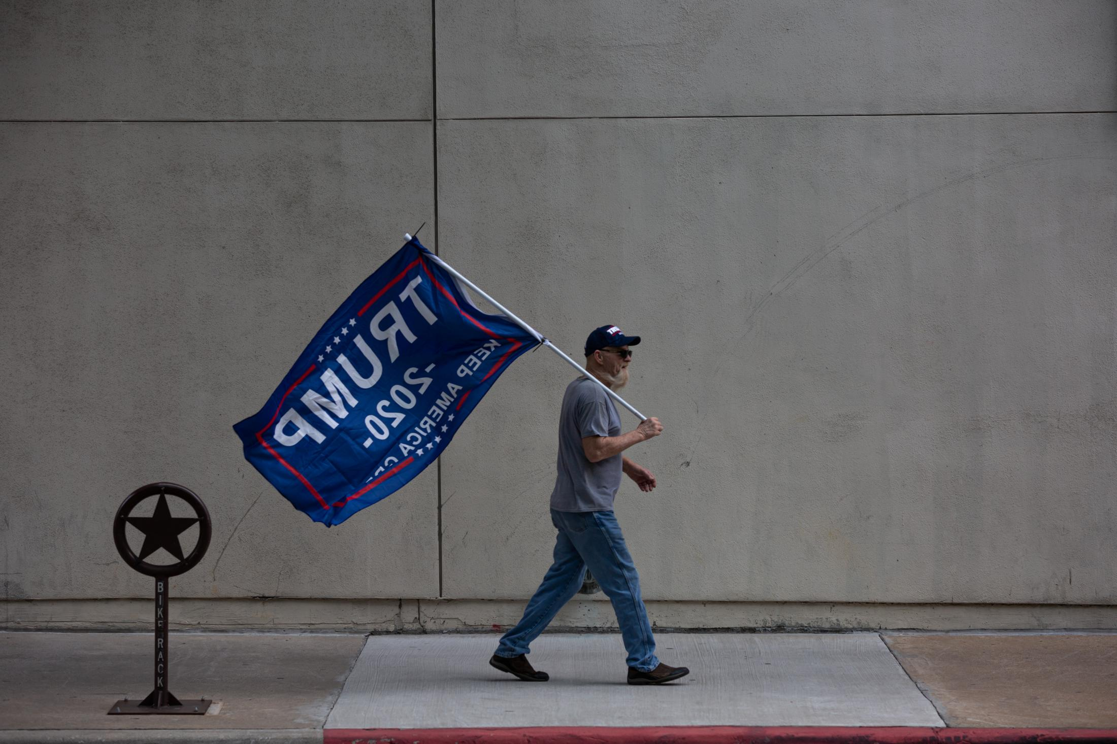 11/14/20 Fort Worth, Texas - A Trump Supporter holds his flags as he walks back to his vehicle after a massive Trump rally against the 2020 Presidential Election.