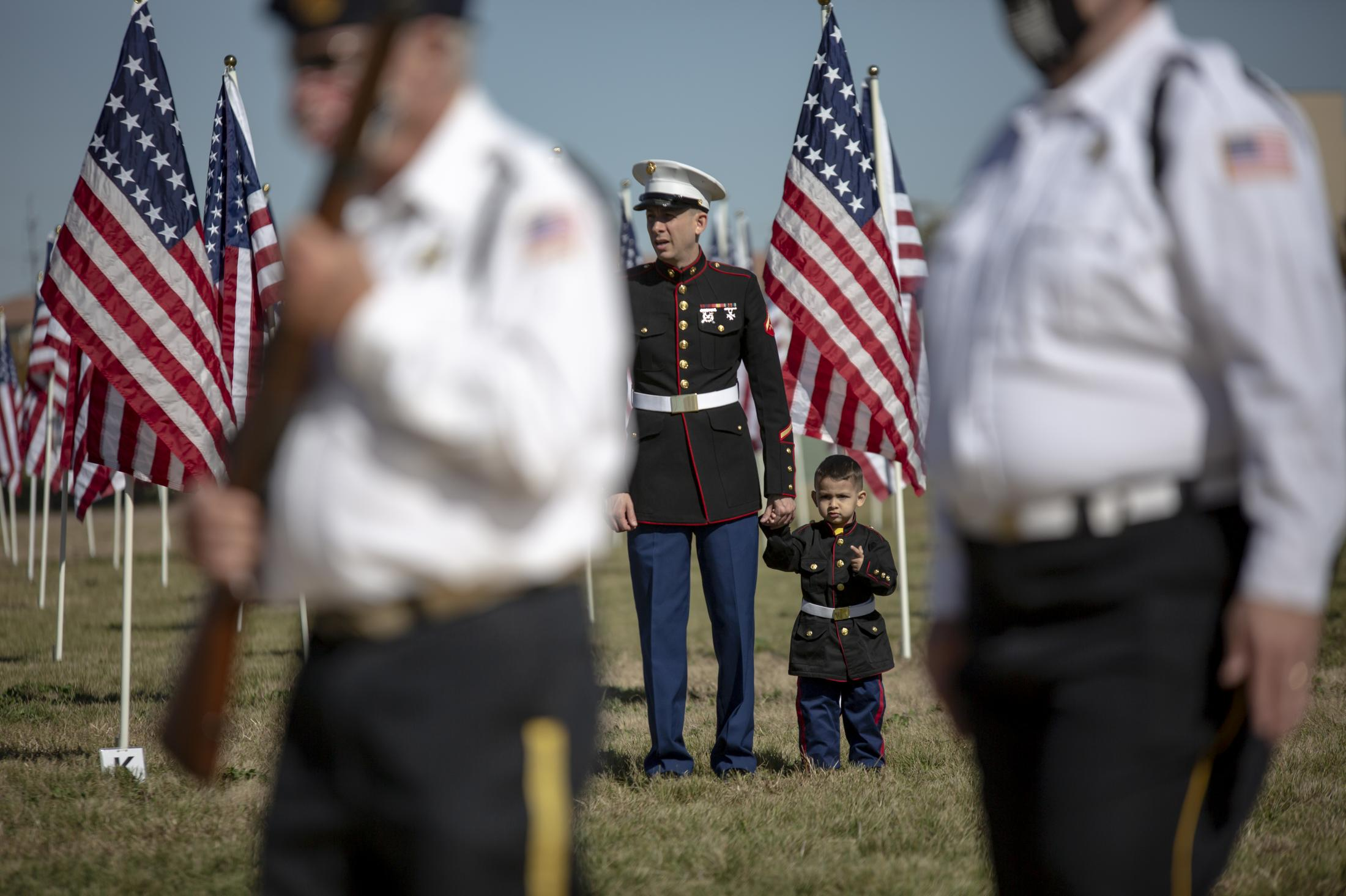 Justin (Right) and his son Grayson stand at attention during a soldier memorial, field of flags ceremony, that remembers the women and men that have served the United States military.