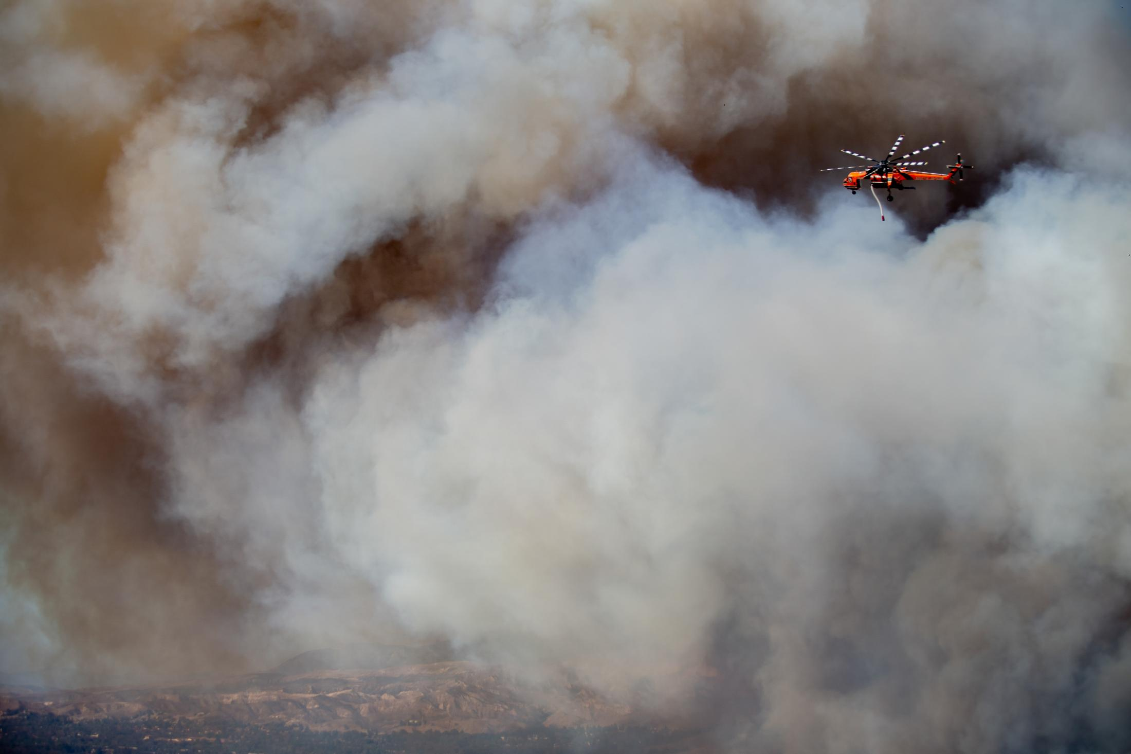 The state of California faced its worst fire season in history. One of the worst fires located in Los Angeles and Ventura County, named the Woolsey Fire. This wildfire burned; 96,949 acres and destroyed 1,643 structures. Three people reported to have died in the blaze, and over a quarter-million evacuated. A helicopter flys above as it make water drops on a new fire breakout.